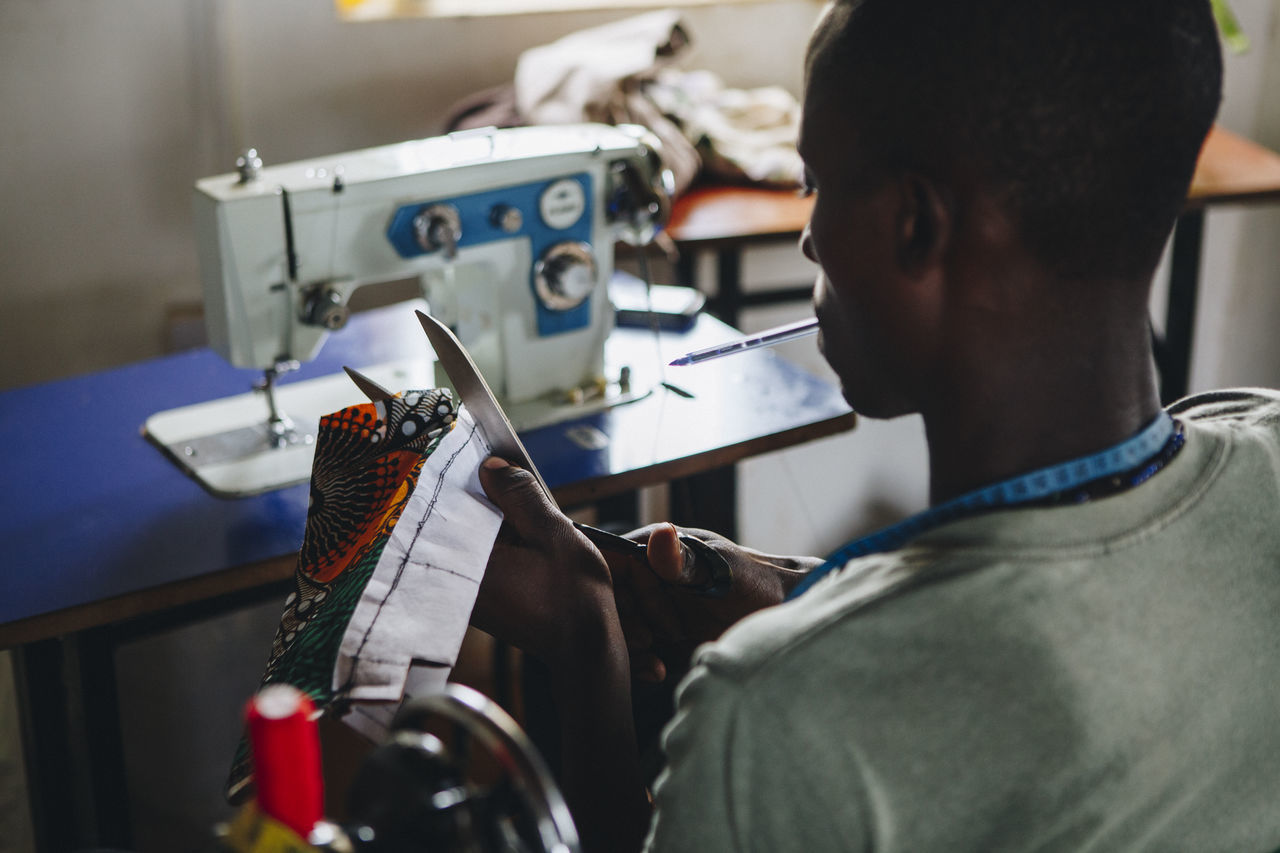 Adult Africa African Clothing Crafting Crafts Craftsman Craftsmanship  Entrepreneur Fabric Indoors  Making Mpigi One Man Only One Person Repairing Scissors Sewing Sewing Machine Sina Skill  Studio Working Workshop Young Adult