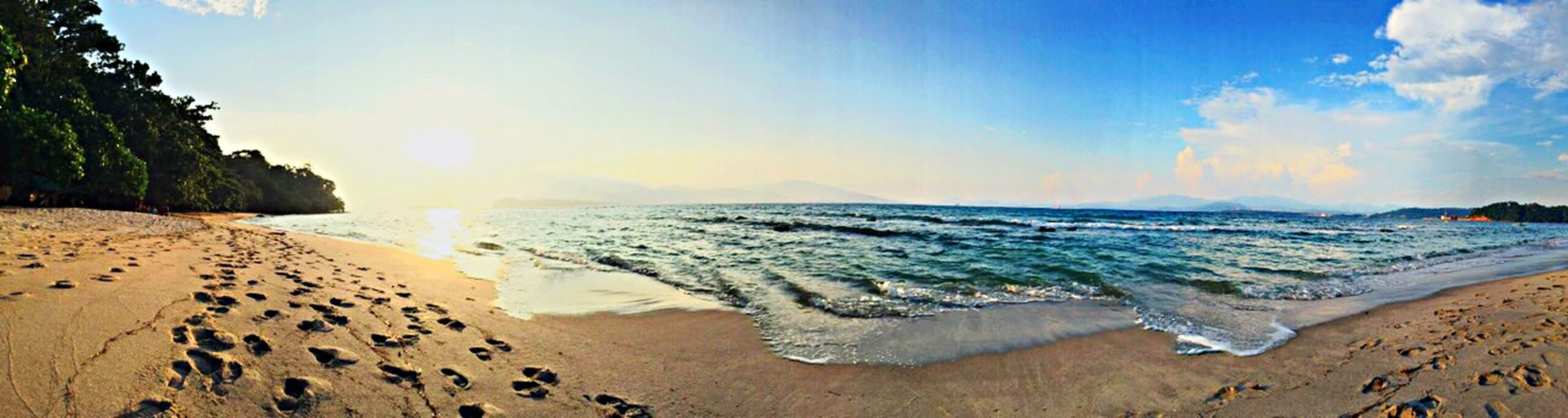 sea, beach, water, horizon over water, shore, sand, scenics, tranquil scene, tranquility, beauty in nature, sky, nature, sunlight, blue, coastline, idyllic, wave, vacations, incidental people, panoramic