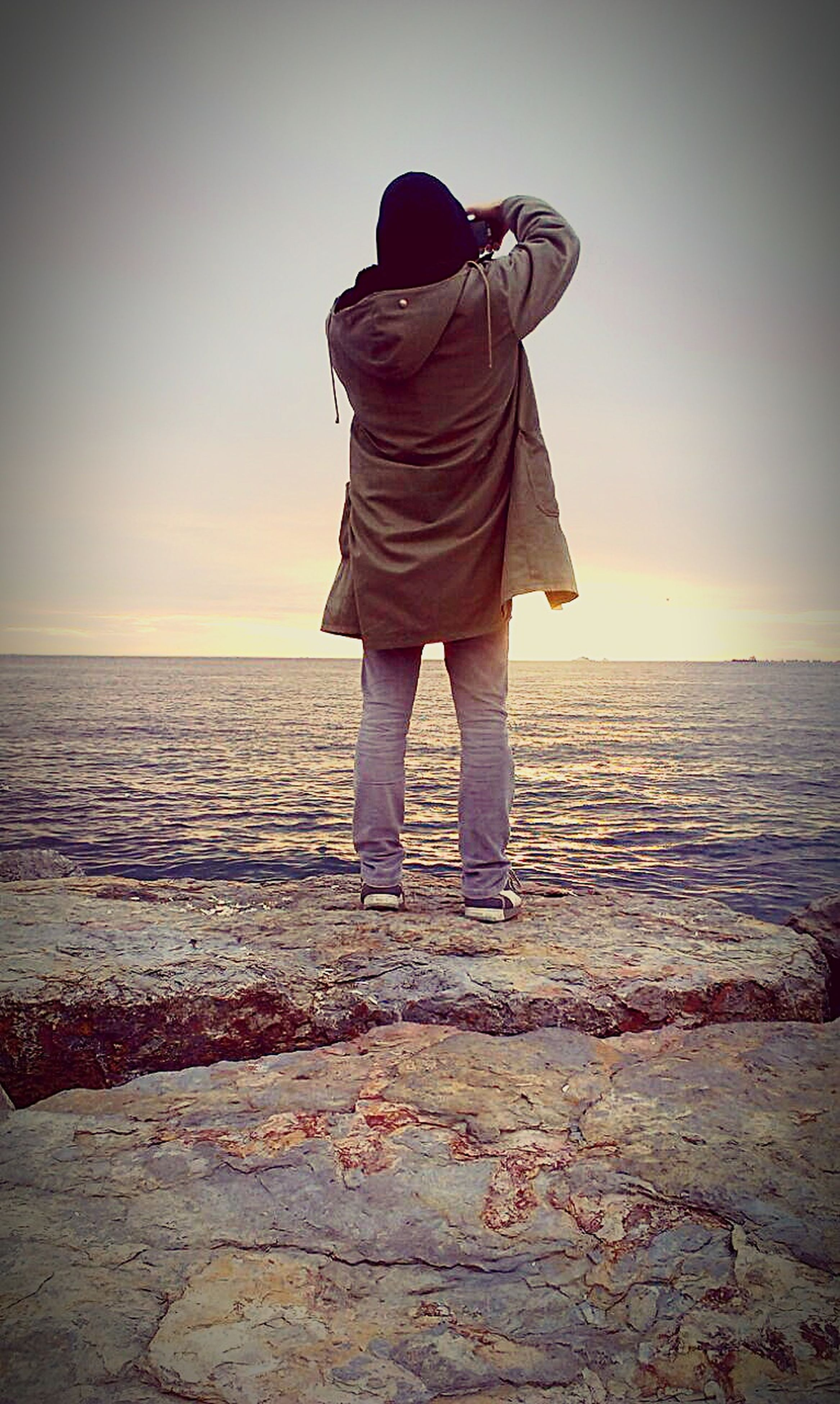 sea, water, rear view, horizon over water, standing, full length, beach, lifestyles, leisure activity, tranquil scene, tranquility, sunset, scenics, shore, beauty in nature, sky, person, casual clothing