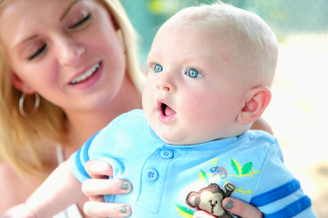 Baby Babyhood Blue Eyes Boy Childhood Cute Day Happiness Headshot Holding Innocence Lifestyles Mother Outdoors People Portrait Real People Son Togetherness Two People Woman