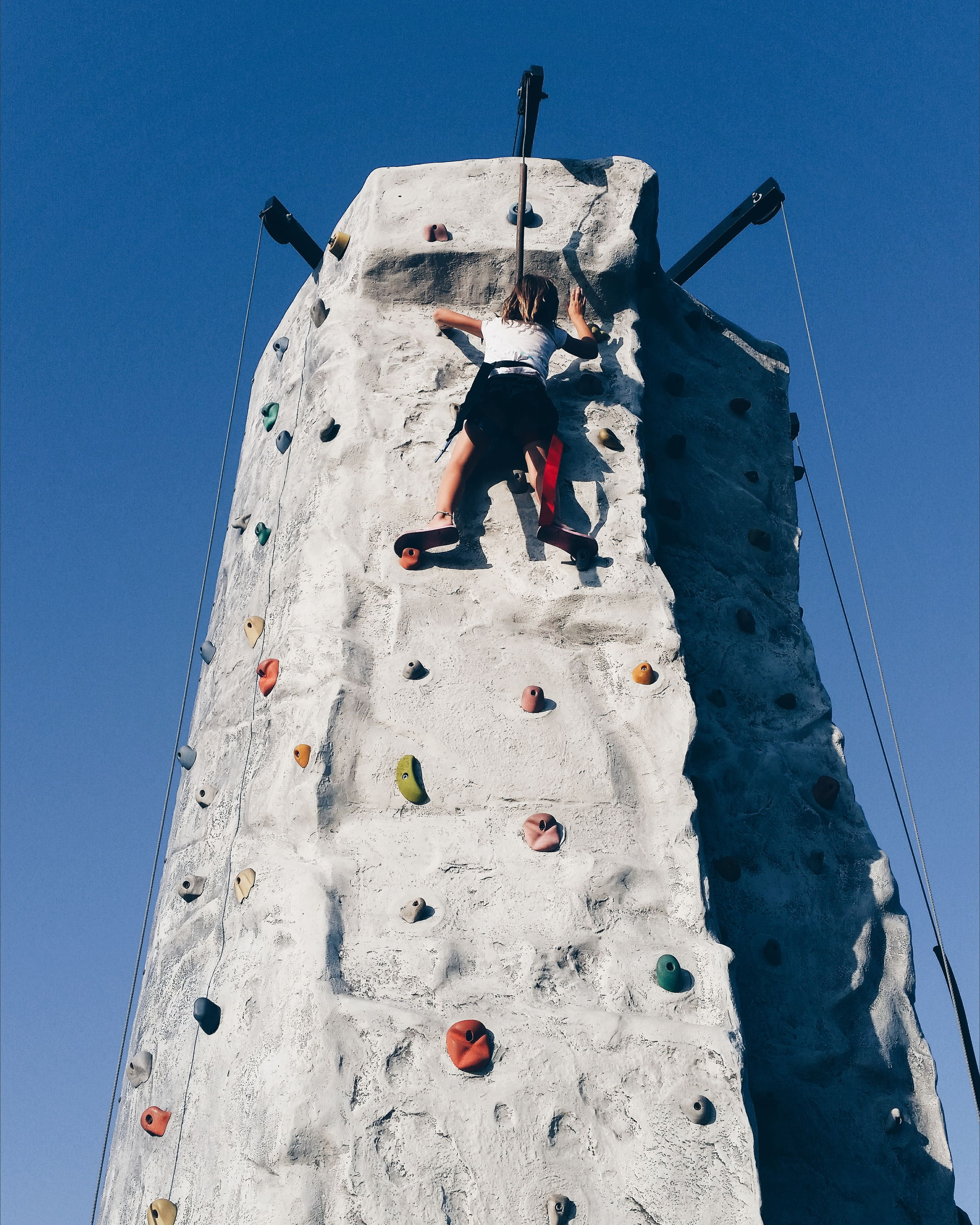 low angle view, climbing, day, sport, leisure activity, real people, sky, adventure, clear sky, climbing wall, blue, full length, outdoors, one person, extreme sports, people
