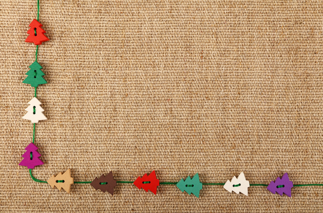 Christmas and new year template of handicraft wooden painted sewing buttons in shape of Xmas tree and thread over canvas background Buttons Canvas Celebration Christmas Christmas Tree Close-up Colorful Copy Space Craft Decor Decoration Design Eco Festive Handicraft Holiday Knitted  Multi Colored Natural New Year Painted Sewing Template Textured  Wooden