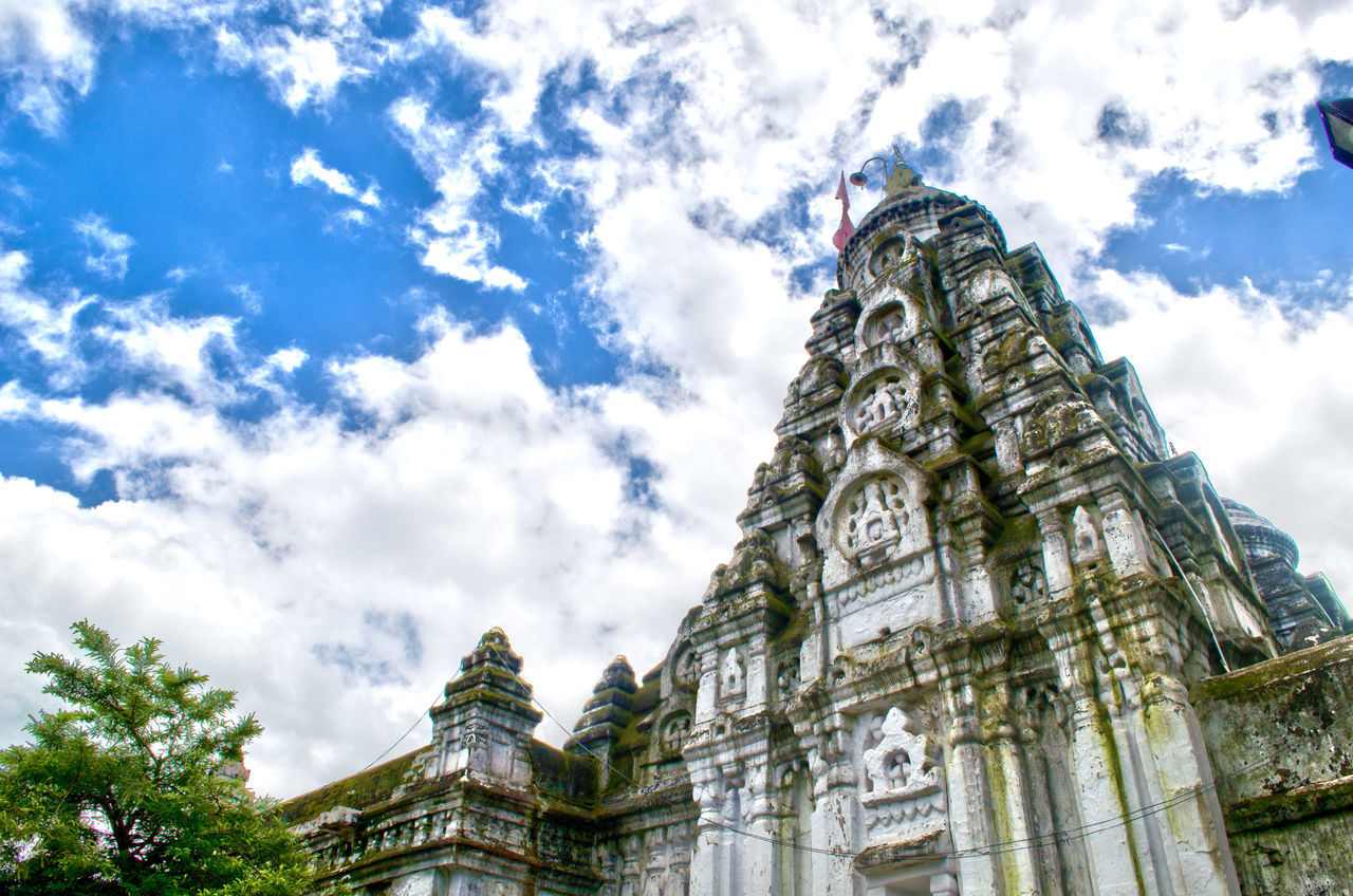 religion, spirituality, place of worship, low angle view, architecture, sky, cloud - sky, building exterior, built structure, history, ancient, day, statue, travel destinations, outdoors, sculpture, no people, ancient civilization, tree