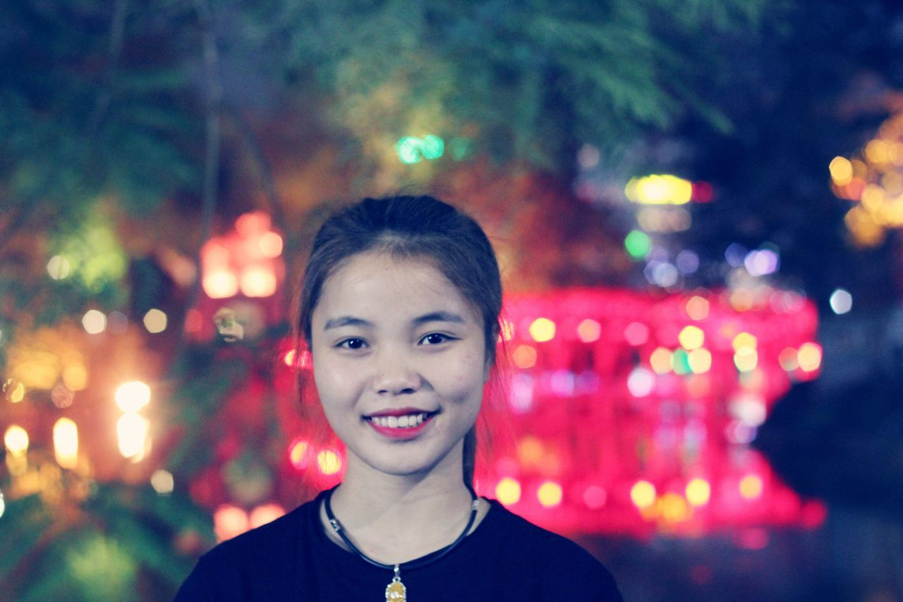 looking at camera, headshot, portrait, focus on foreground, illuminated, one person, smiling, childhood, front view, real people, happiness, night, outdoors, close-up, people