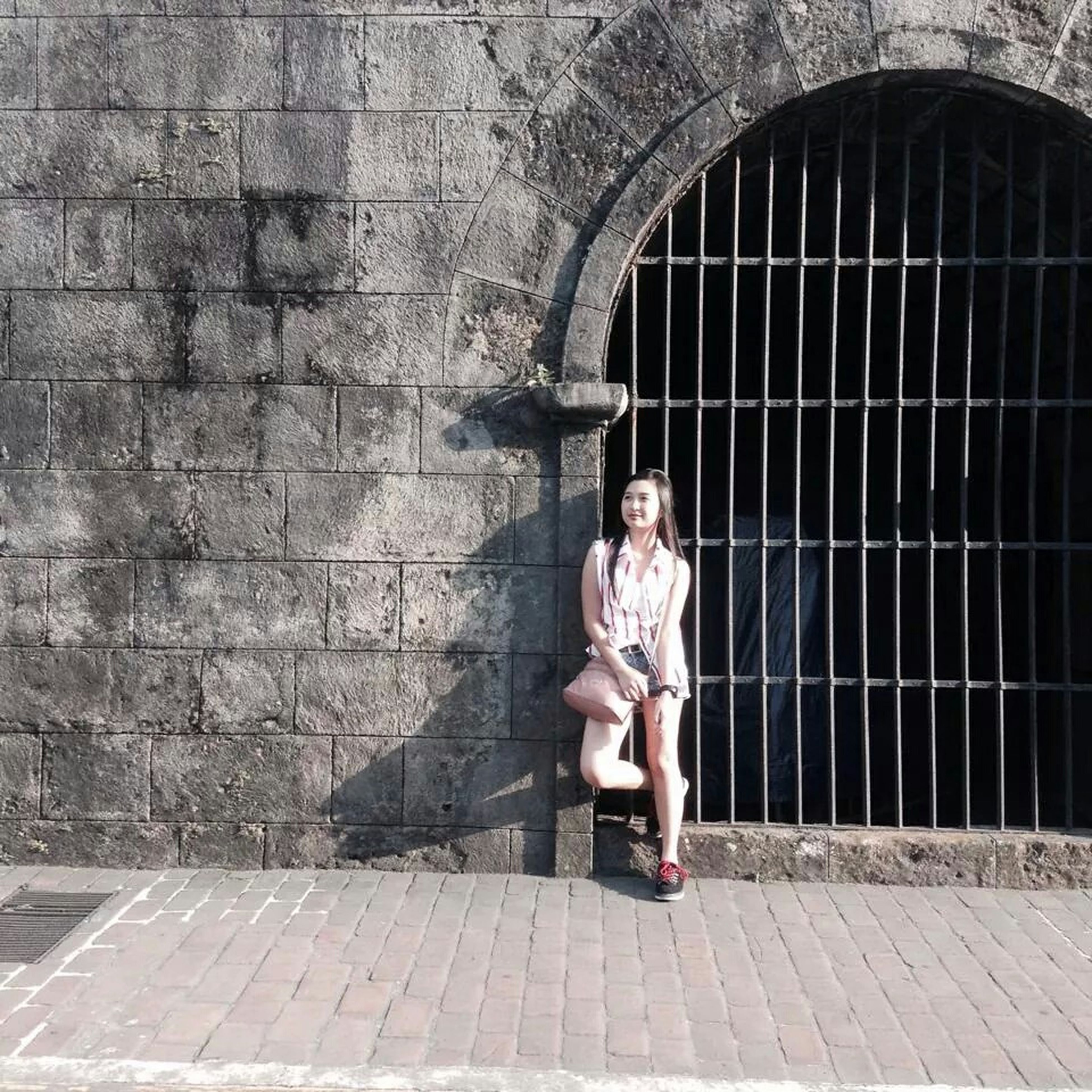young adult, person, lifestyles, full length, young women, casual clothing, looking at camera, leisure activity, portrait, architecture, front view, built structure, standing, brick wall, wall - building feature, smiling, building exterior