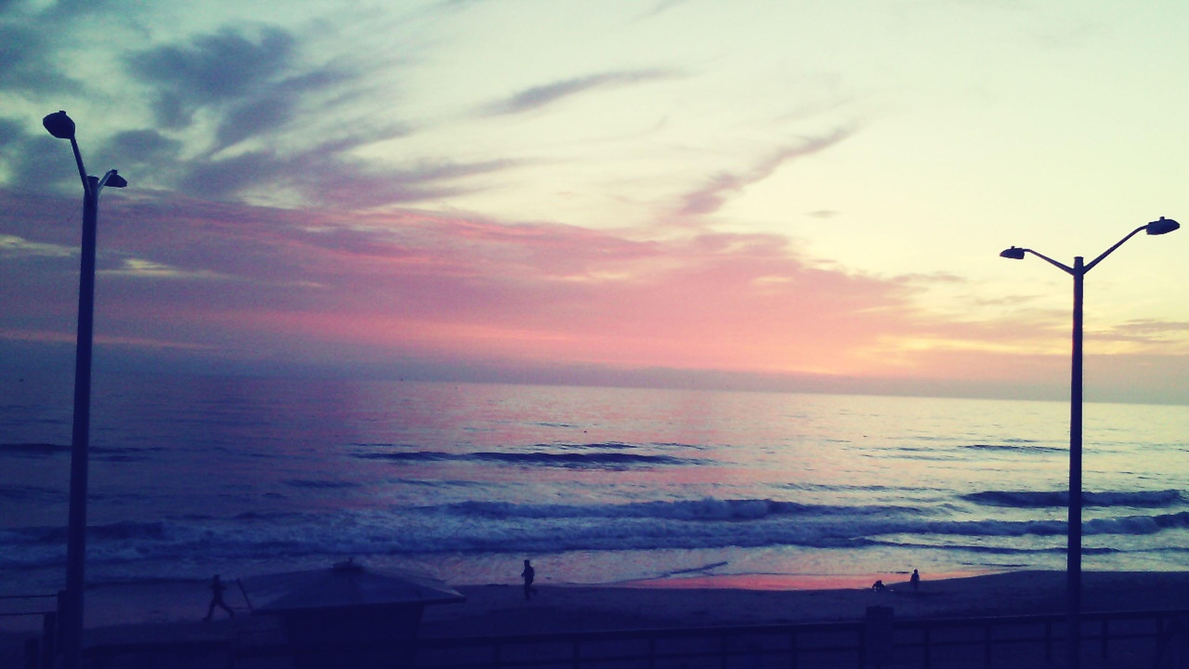 sea, horizon over water, sunset, sky, water, street light, scenics, beauty in nature, tranquility, tranquil scene, silhouette, lighting equipment, nature, idyllic, orange color, beach, cloud - sky, shore, outdoors, dusk