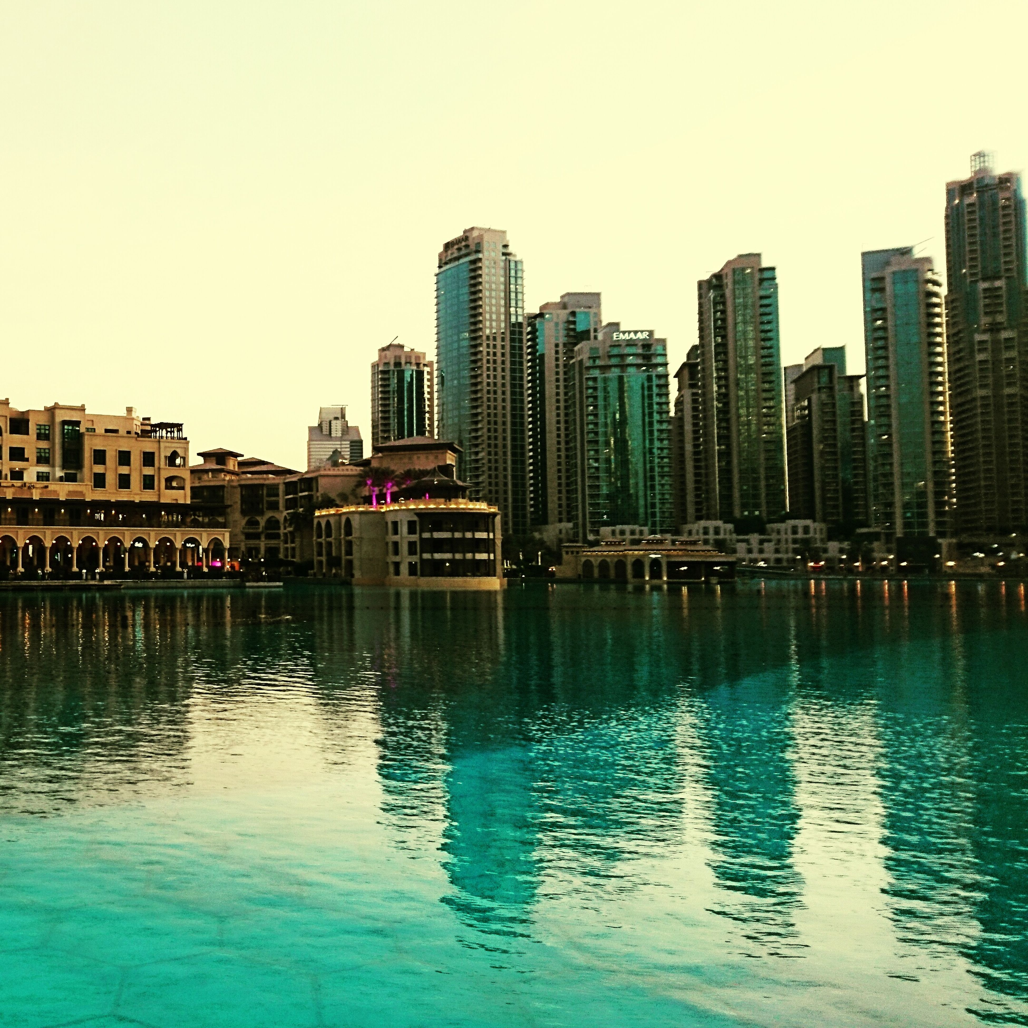 building exterior, city, architecture, reflection, built structure, skyscraper, modern, cityscape, urban skyline, clear sky, outdoors, waterfront, water, city life, travel destinations, financial district, downtown district, sky, river, no people, day