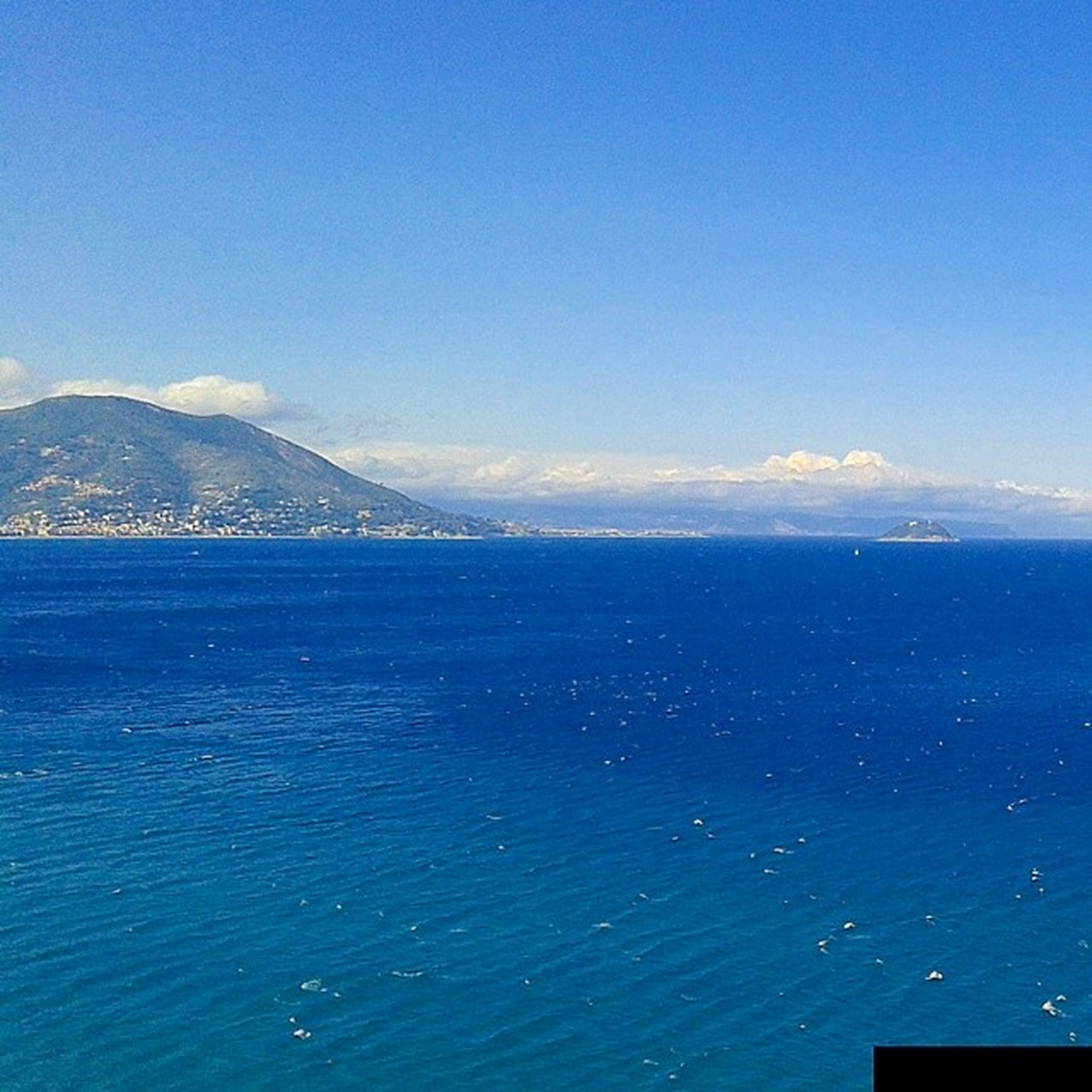 blue, water, sea, tranquil scene, scenics, tranquility, beauty in nature, mountain, nature, copy space, waterfront, idyllic, clear sky, sky, horizon over water, mountain range, calm, seascape, outdoors, remote