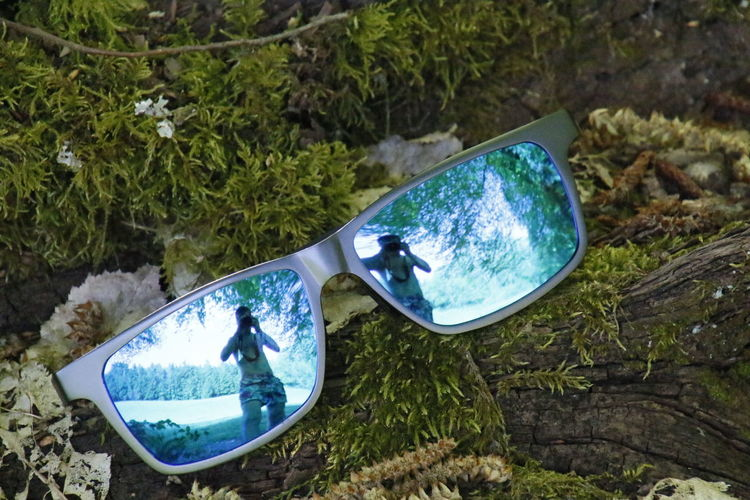 Beauty In Nature Blue Boat Close-up Day Discard Grass Green Color Growth Lakeshore Nature No People Non-urban Scene Outdoors Plant Sun Glasses Tranquil Scene Tranquility Water