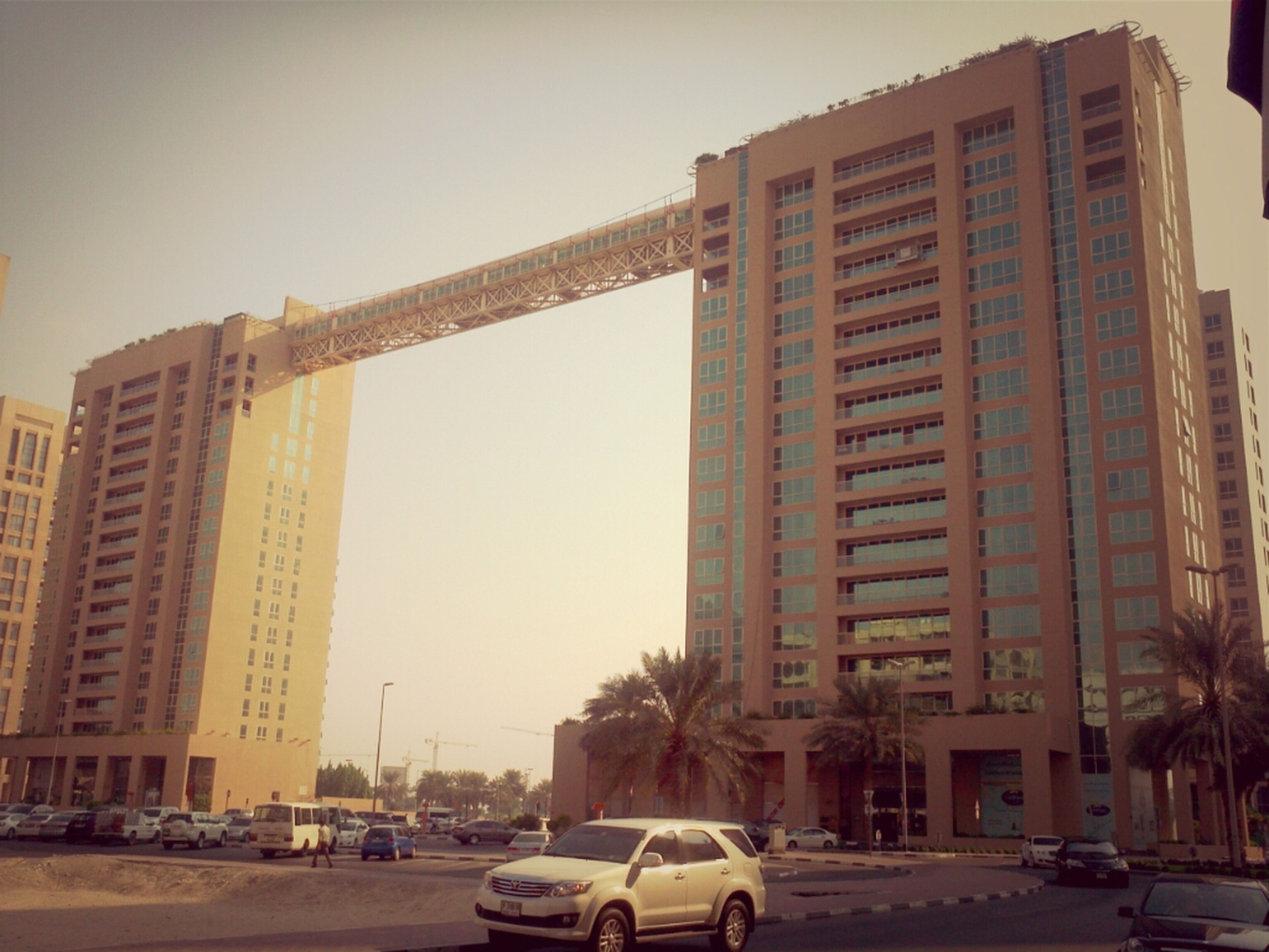 building exterior, architecture, built structure, car, land vehicle, transportation, mode of transport, city, street, clear sky, building, road, city life, parking, city street, incidental people, stationary, parked, street light, low angle view