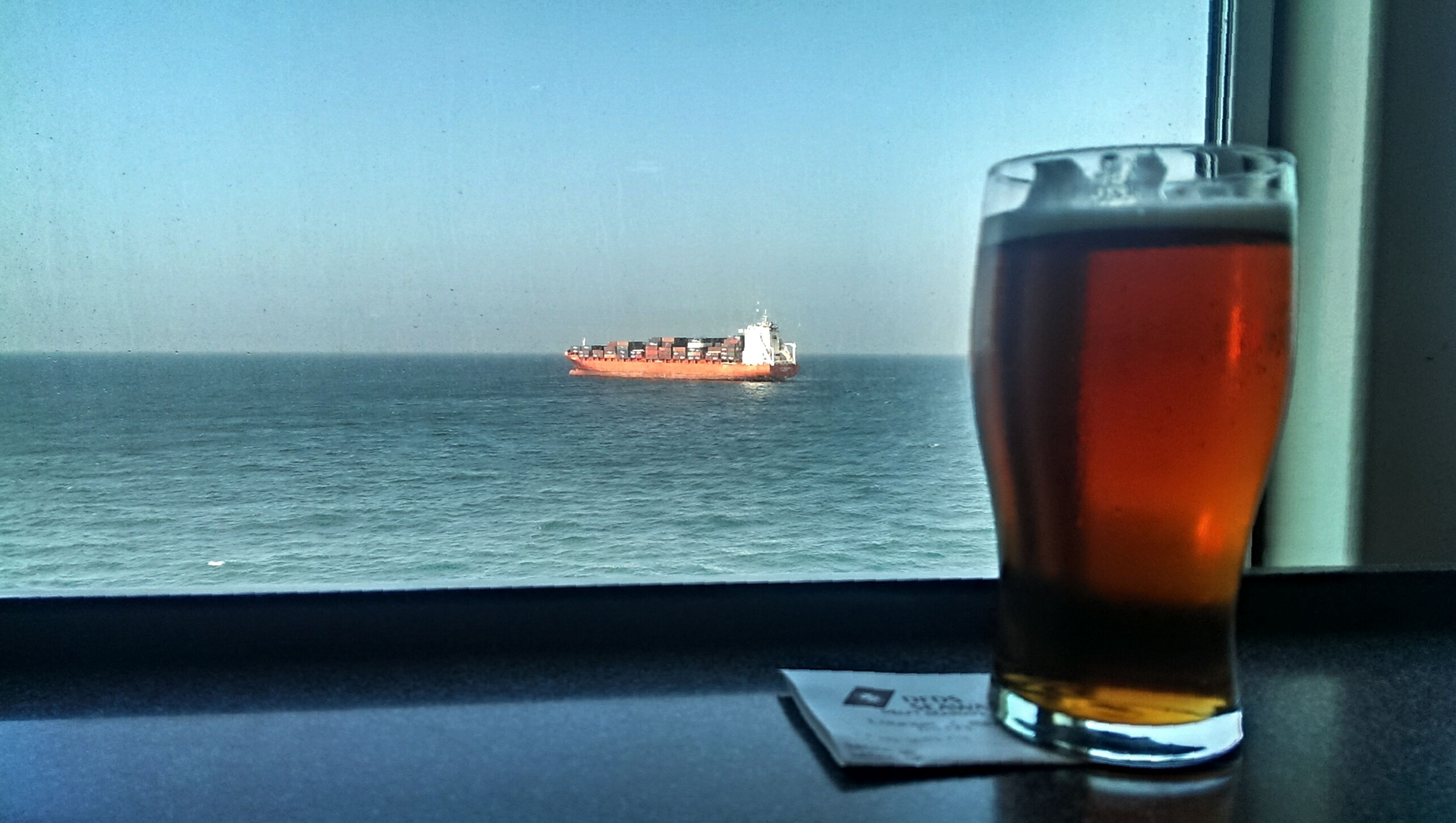 sea, water, horizon over water, drink, refreshment, nautical vessel, food and drink, sky, transportation, mode of transport, boat, table, scenics, transparent, sunlight, window, day, nature, outdoors, drinking glass