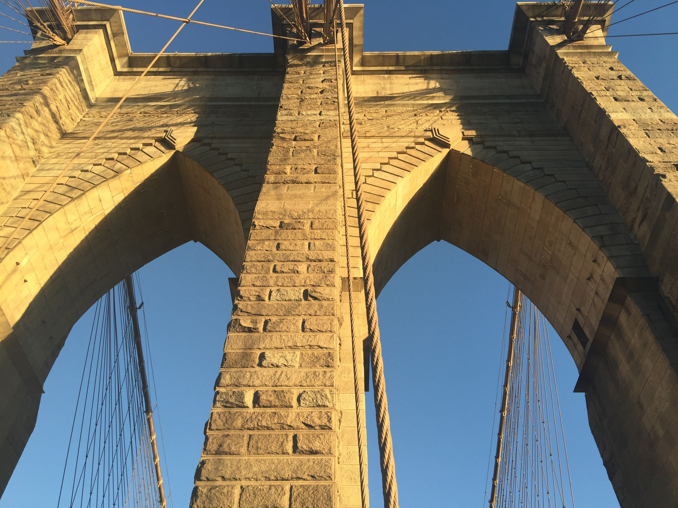 low angle view, architecture, built structure, clear sky, connection, blue, building exterior, sky, engineering, bridge - man made structure, outdoors, history, day, sunlight, arch, no people, famous place, bridge, travel destinations, cable