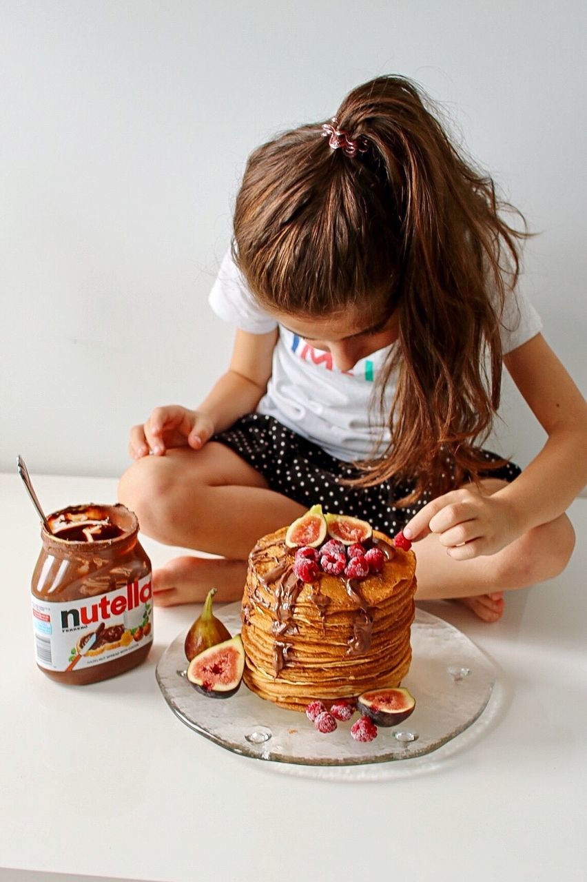 sweet food, dessert, food, food and drink, real people, unhealthy eating, one person, indulgence, cake, table, plate, temptation, sitting, leisure activity, ready-to-eat, freshness, indoors, childhood, girls, lifestyles, day, people