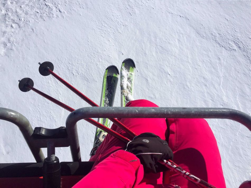 View from above of woman skier in the teleski wearing gloves and holding ski poles Real People Sport Leisure Activity Outdoors Day Nature Winter Snow Slope Mountains Teleski Skilift Skier Woman Feet Legs Hand Gloves Hold Skipoles Transport Air Topview
