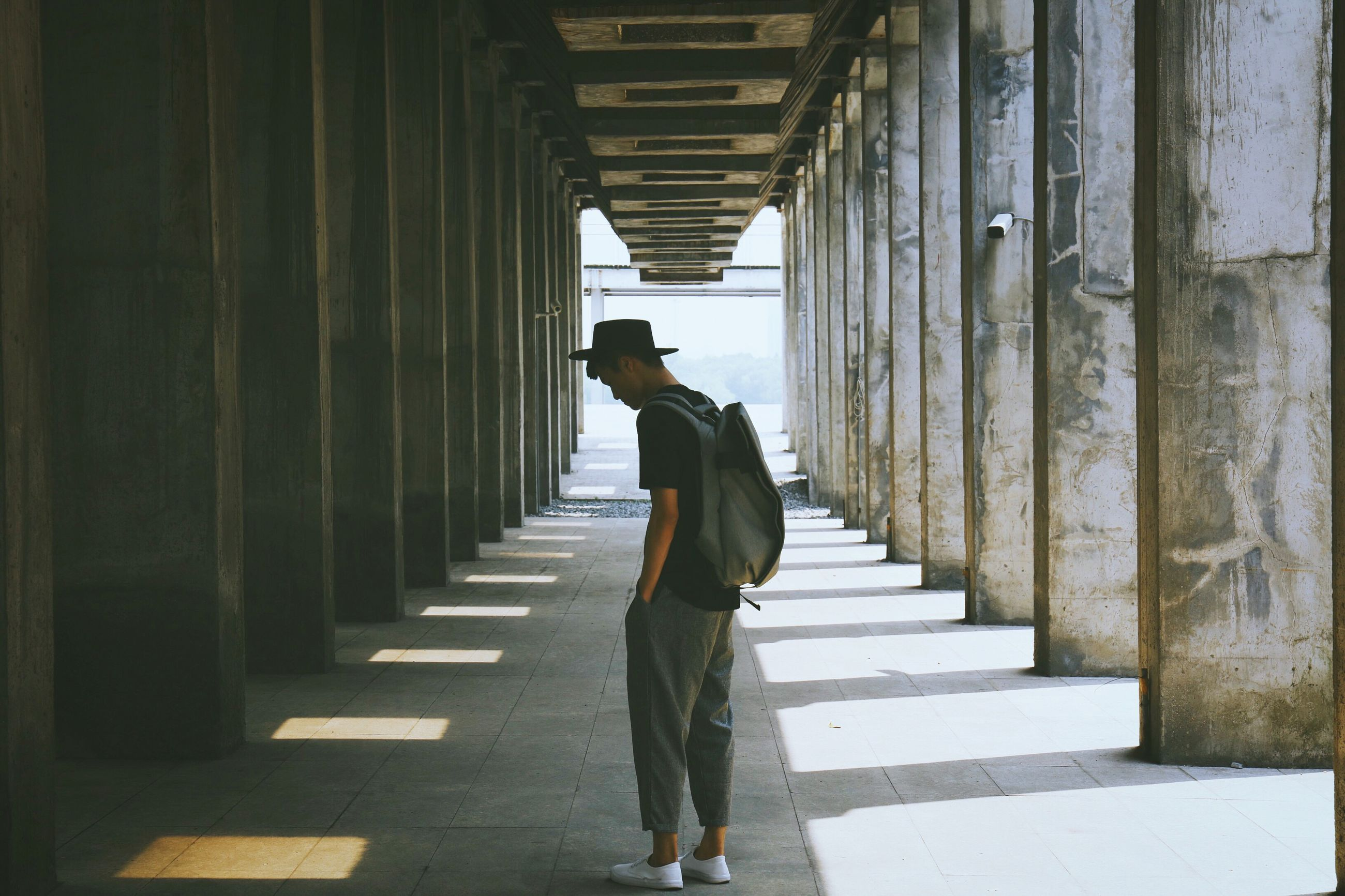 full length, lifestyles, casual clothing, architecture, corridor, leisure activity, indoors, built structure, in a row, the way forward, colonnade, day, architectural column, young adult, well-dressed, narrow