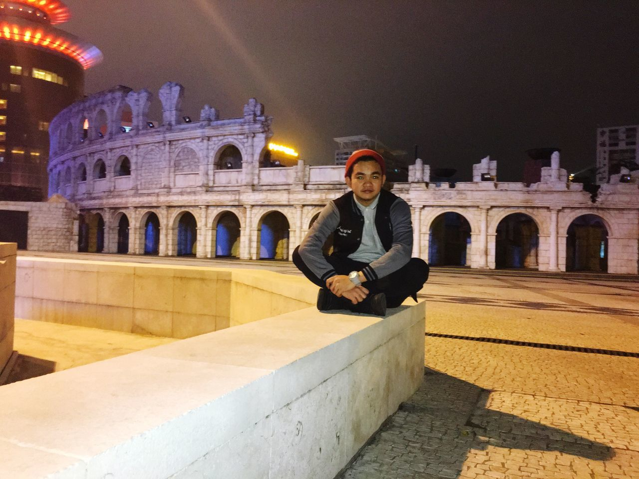 architecture, night, built structure, history, real people, illuminated, lifestyles, tourism, smiling, travel, building exterior, travel destinations, portrait, leisure activity, arch, young women, outdoors, looking at camera, mature adult, young adult, one person, city, happiness, full length, ancient civilization, sky, adult, people