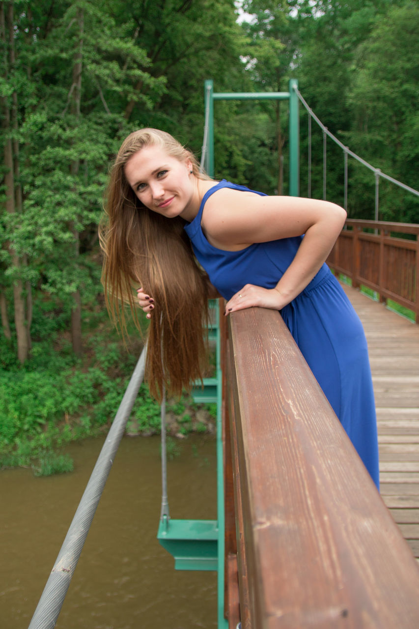 Side View Portrait Of Beautiful Woman Leaning On Wooden Bridge Over River
