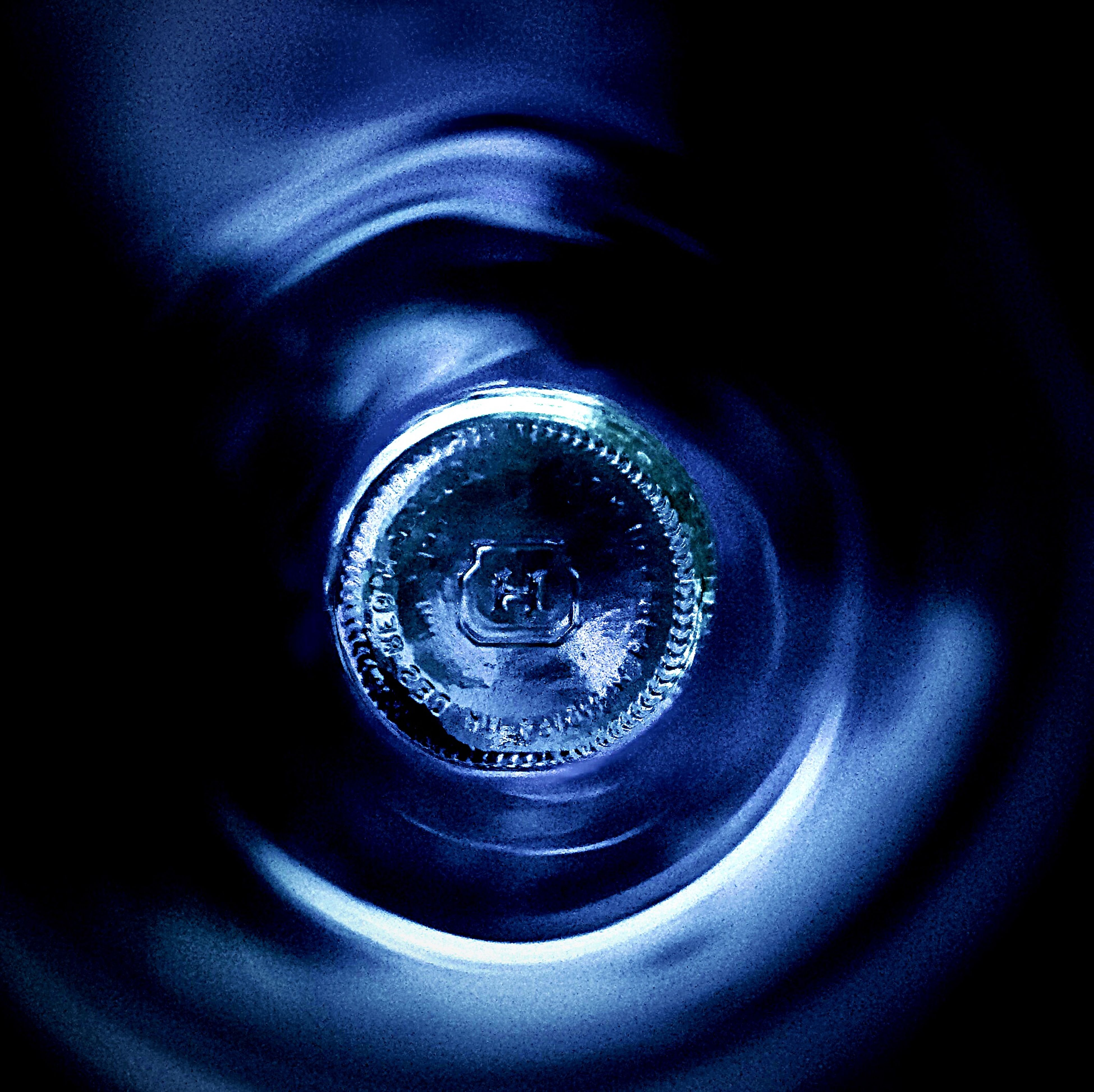 indoors, close-up, metal, single object, technology, circle, no people, part of, still life, studio shot, metallic, selective focus, high angle view, illuminated, blue, pattern, equipment, focus on foreground, shiny, black background