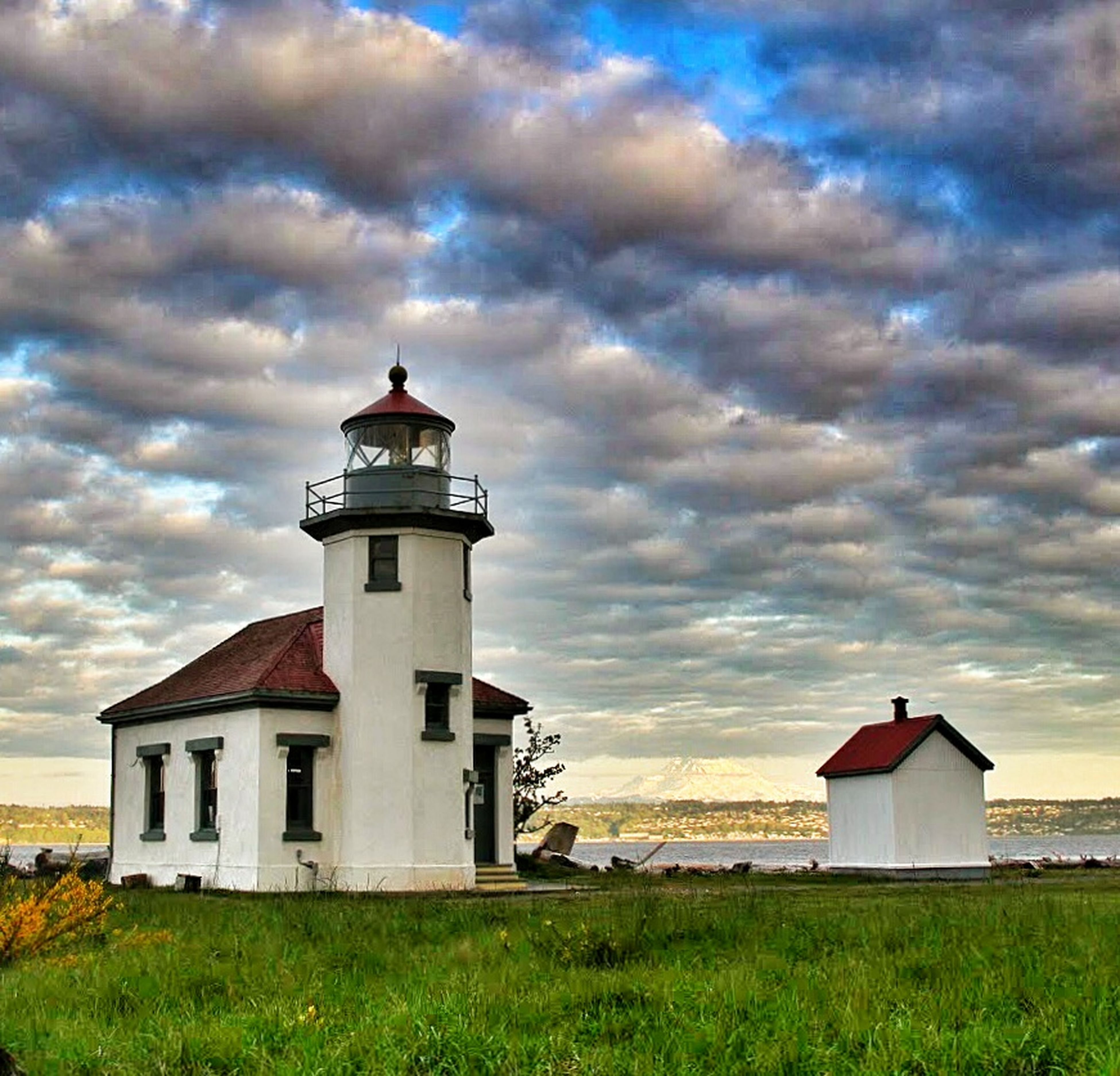 lighthouse, architecture, building exterior, built structure, sky, cloud - sky, grass, guidance, cloudy, protection, security, safety, field, cloud, direction, house, nature, landscape, tranquil scene, tower