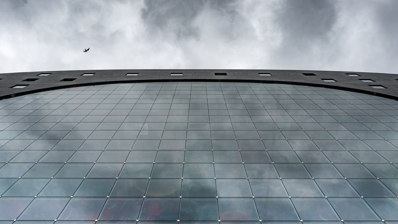 Looking up at glass, steel and a gull... Architecture Building Exterior Built Structure Business City Cloud - Sky Cold Copy Space Dark Day Low Angle View Markthal Modern Netherlands No People Outdoors Reflection Rotterdam Sky The Architect - 2017 EyeEm Awards Trade Travel Destinations