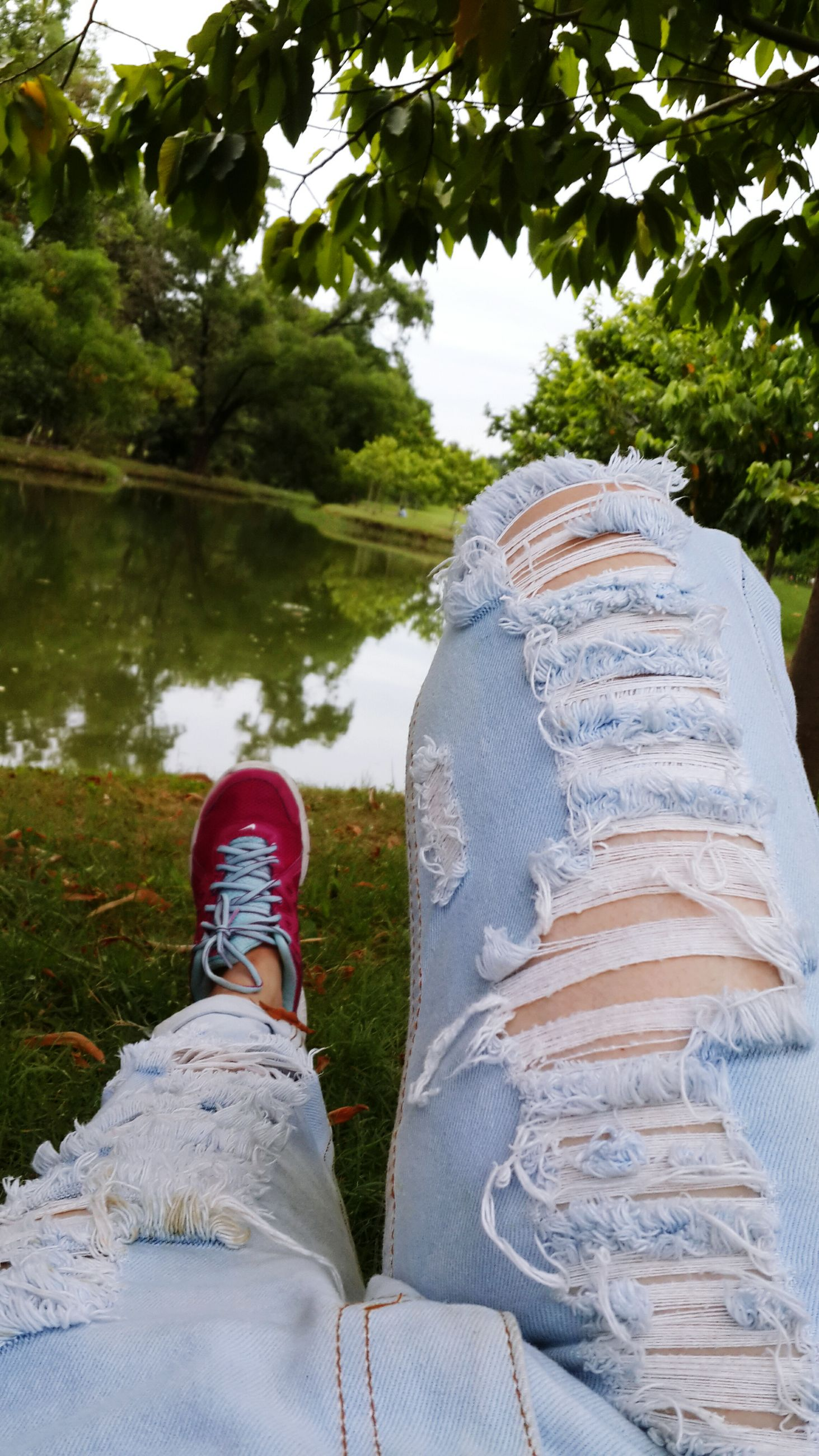 low section, shoe, water, person, personal perspective, tree, rock - object, footwear, nature, outdoors, day, tranquility, beauty in nature, standing, lake, stone - object, jeans, men