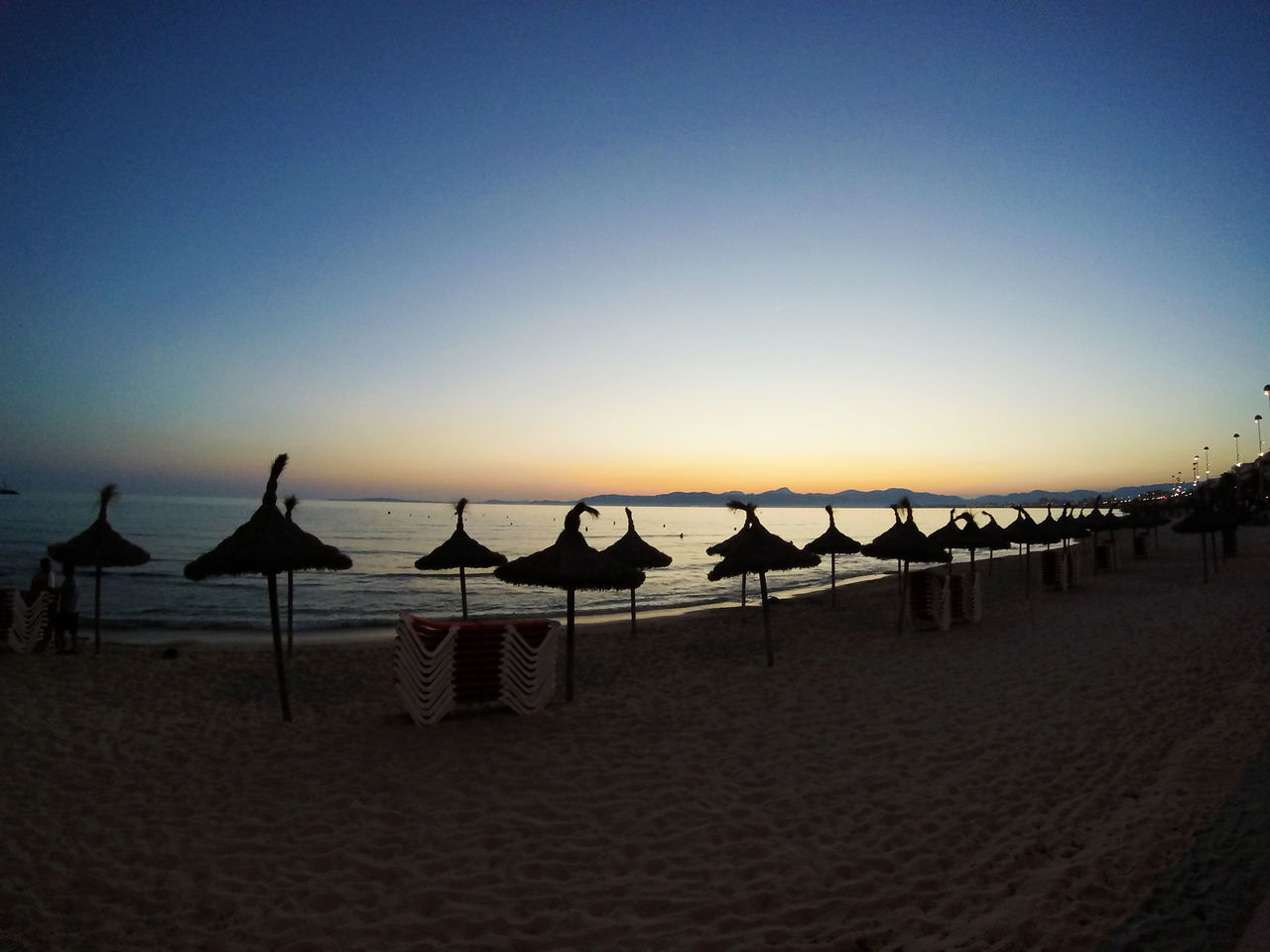 beach, sea, sand, shore, tranquility, nature, water, beauty in nature, horizon over water, tranquil scene, clear sky, in a row, scenics, outdoors, sunset, summer, vacations, sun lounger, canopy, sky, silhouette, no people, blue, day