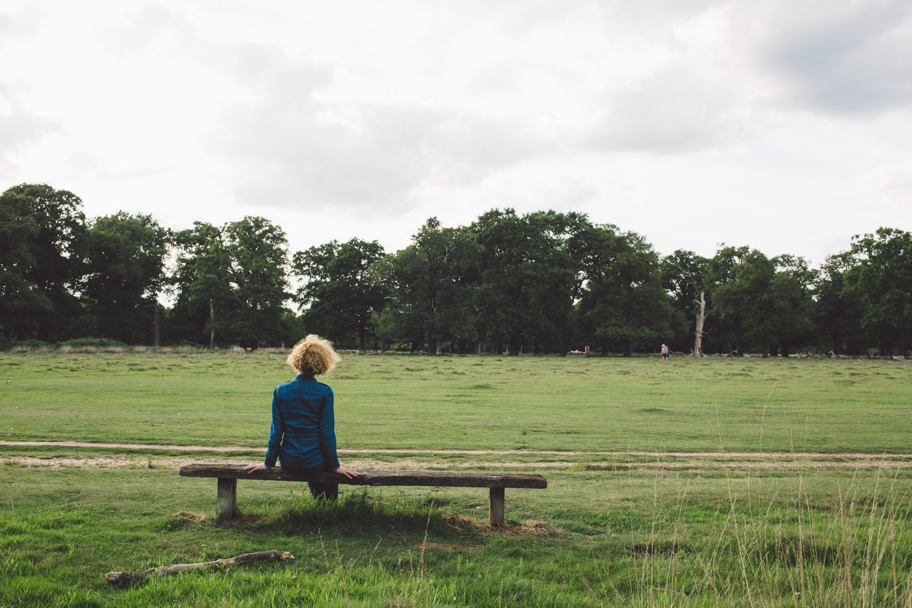 tree, sitting, one person, grass, childhood, casual clothing, landscape, field, sky, tranquil scene, full length, real people, growth, day, green color, nature, tranquility, scenics, beauty in nature, outdoors, people