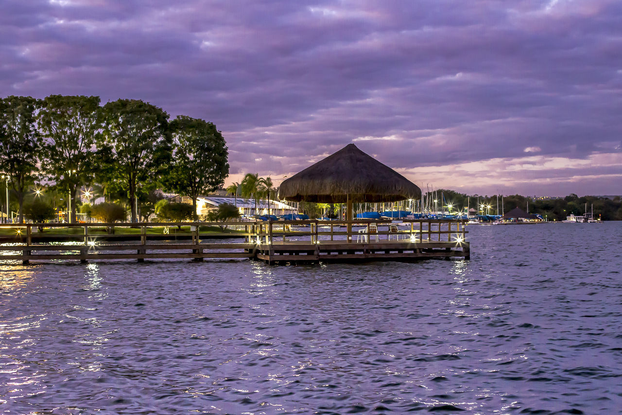 Thatched Roof On Pier By Lake Against Cloudy Sky At Dusk
