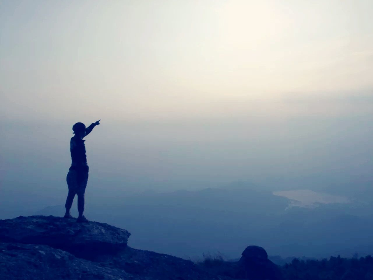Full Length Of Person Pointing In Sky While Standing On Mountain