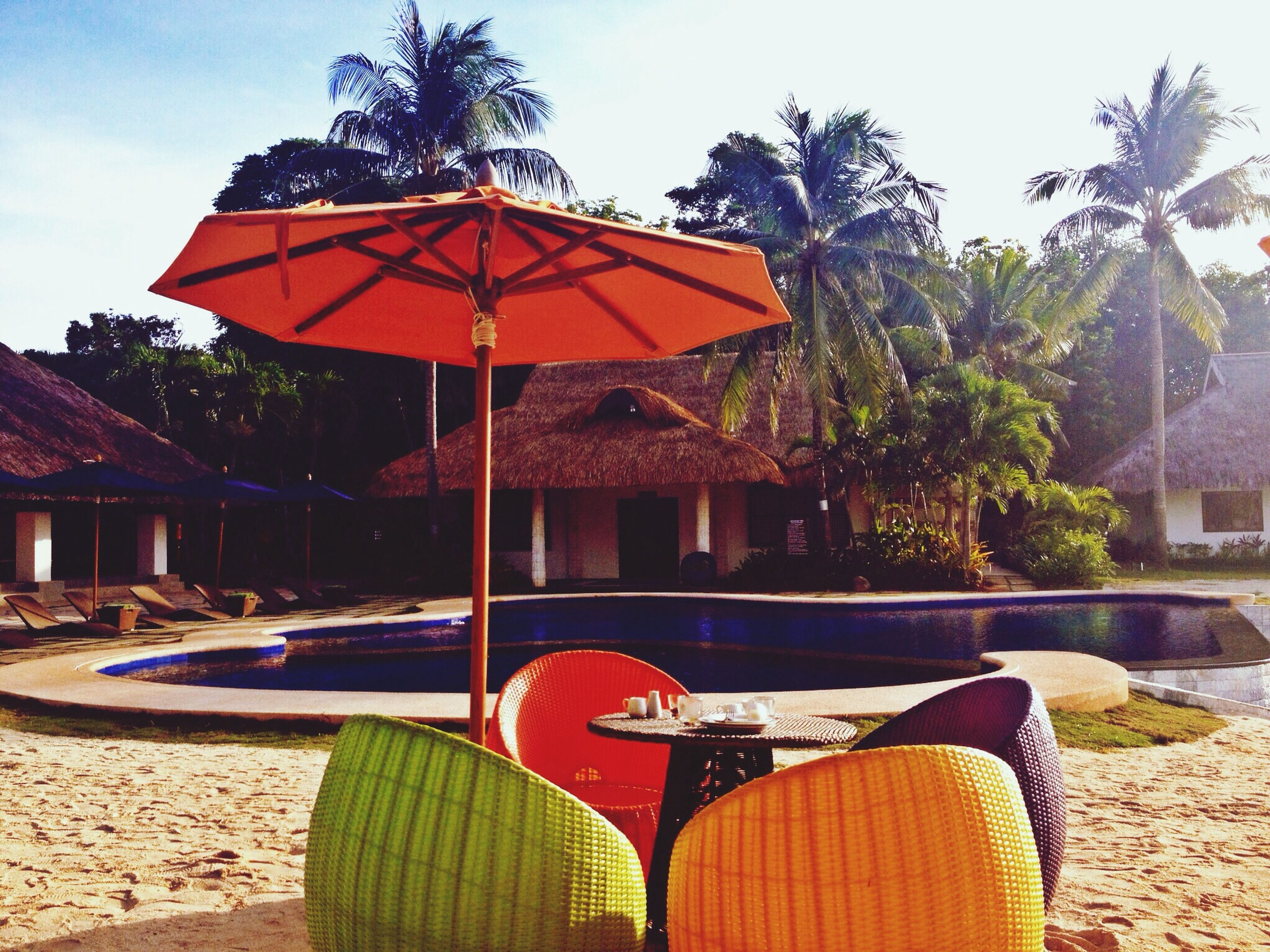 building exterior, built structure, architecture, tree, chair, beach, sunlight, absence, sky, parasol, sand, clear sky, day, house, table, outdoors, sunshade, beach umbrella, red, no people