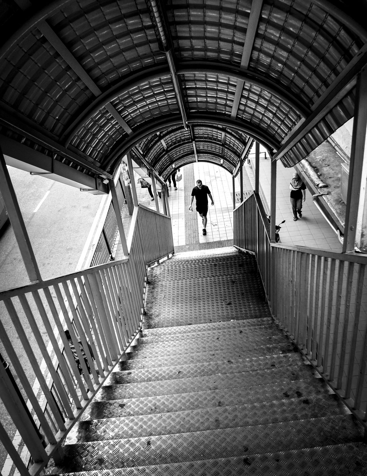 Man about to walk up flight of stairs of an overhead bridge Arch Architecture Ascending B&w Street Photography Black And White Built Structure City Looking Down Man Perspective Railing Stairs Steps Streetphotography Tunnel Urbanphotography Walking