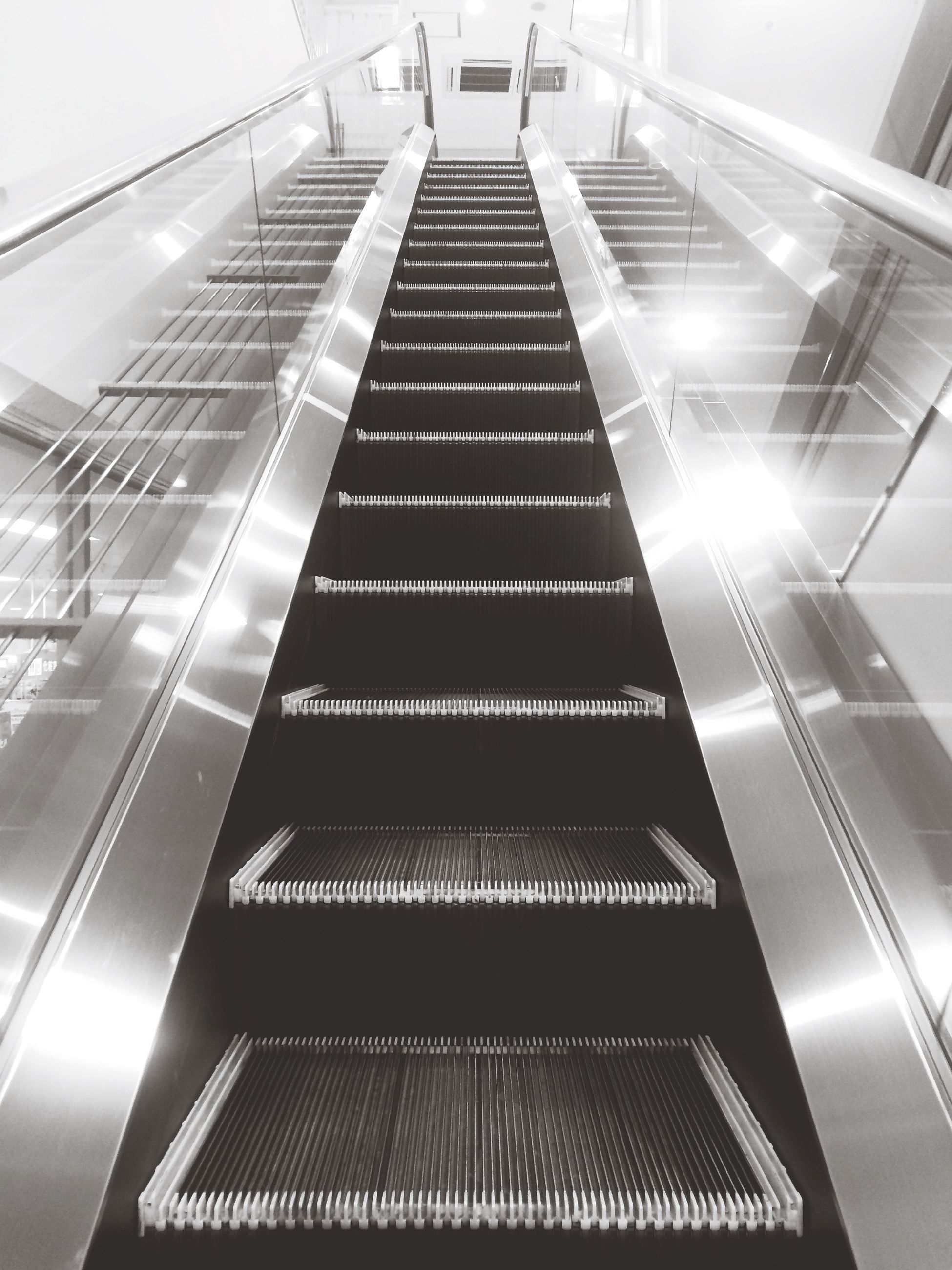 low angle view, architecture, modern, built structure, steps and staircases, indoors, staircase, railing, steps, building exterior, building, sunlight, reflection, escalator, office building, glass - material, city, diminishing perspective, no people, the way forward