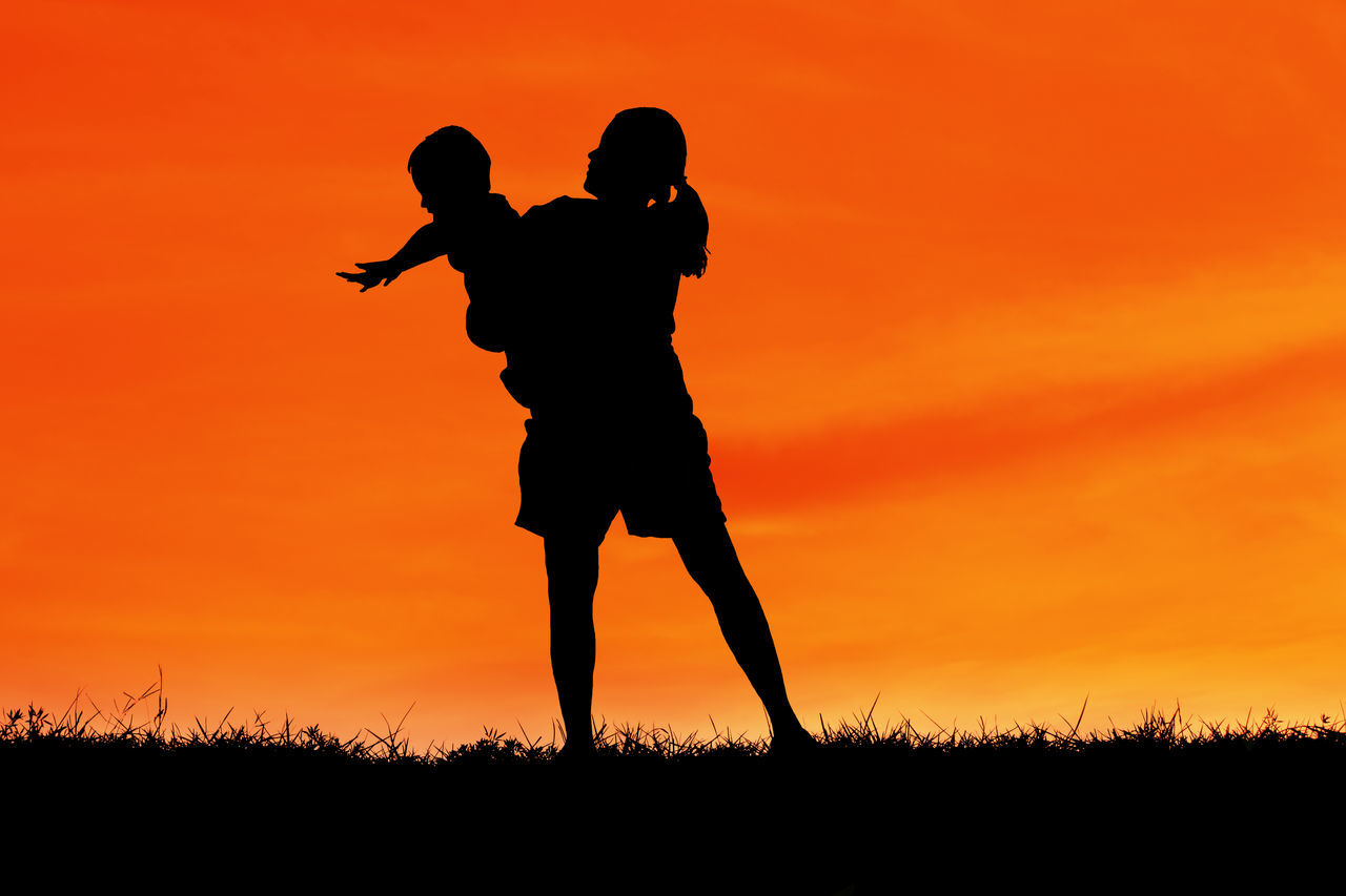 Mother And Child Against Orange Sky During Sunset