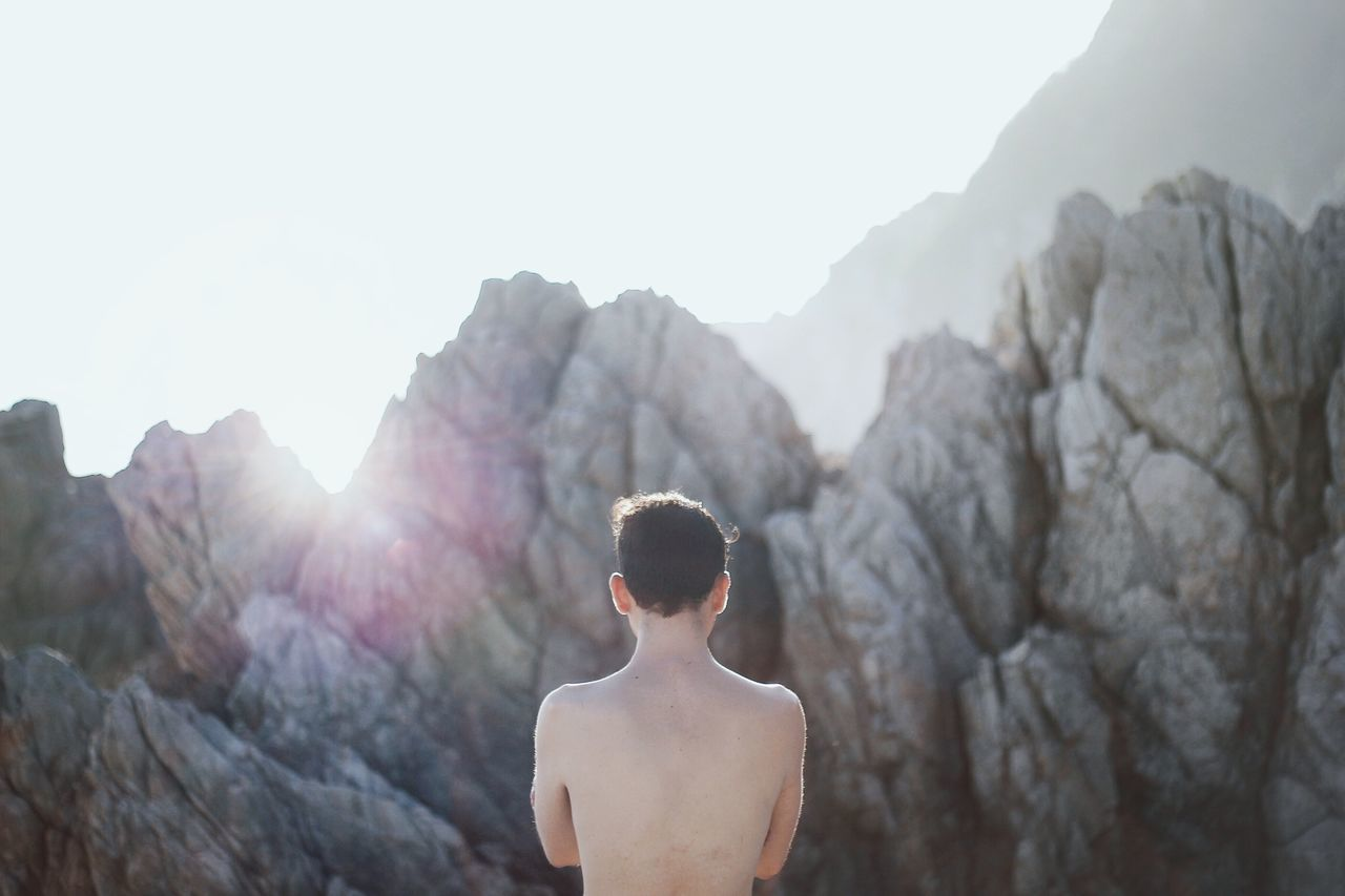 Rear View Of Shirtless Man Standing By Rocks Against Sky