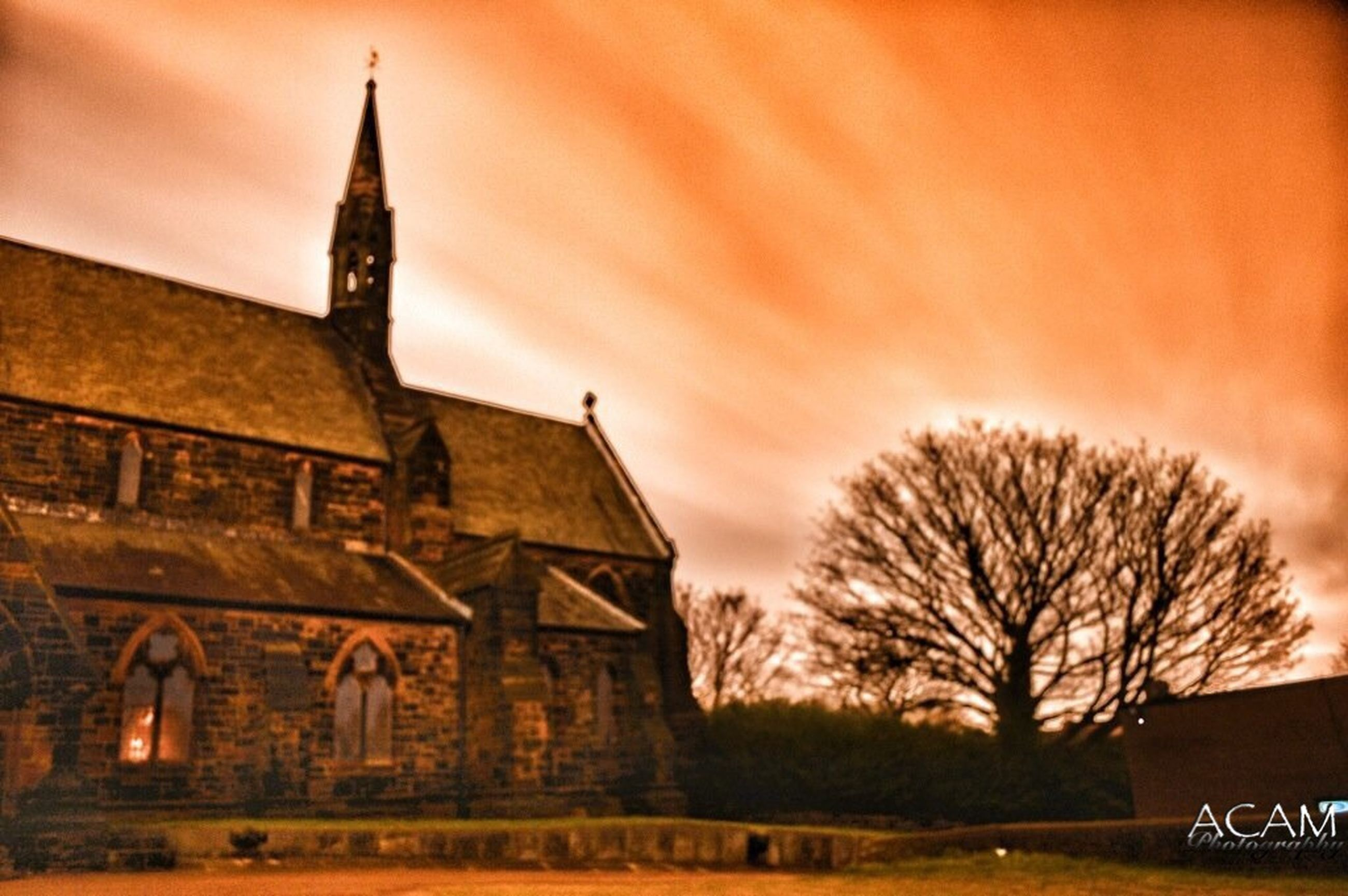 building exterior, architecture, built structure, tree, church, religion, place of worship, bare tree, sunset, low angle view, sky, spirituality, branch, outdoors, orange color, history, no people, cross