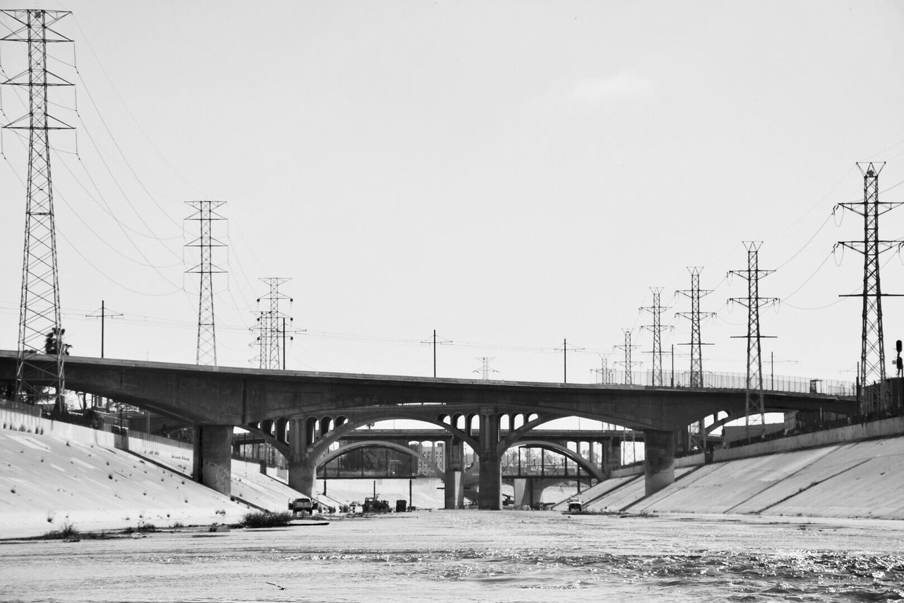 connection, bridge - man made structure, transportation, engineering, electricity pylon, built structure, cable, road, day, architecture, bridge, outdoors, mode of transport, clear sky, sky, low angle view, winter, no people, nature