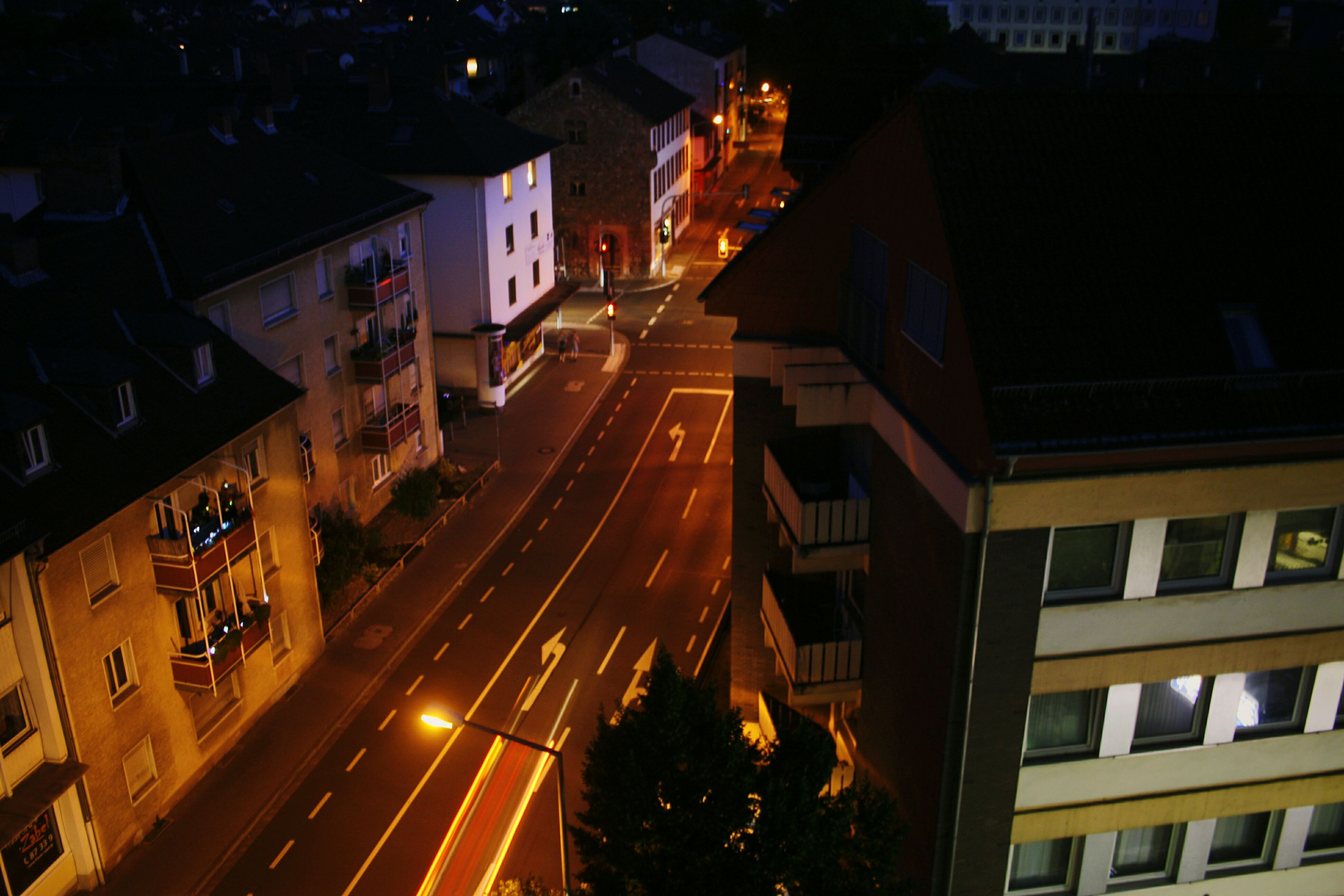 night, illuminated, building exterior, city, architecture, high angle view, built structure, street, city life, transportation, road, city street, residential building, residential structure, car, building, outdoors, incidental people, traffic, land vehicle