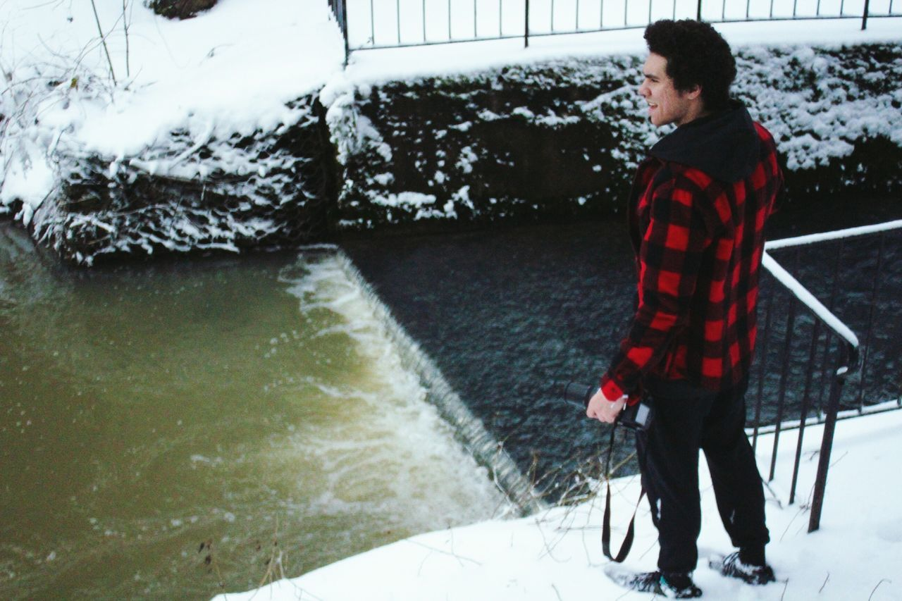 High Angle View Of Man Looking At River Flowing During Winter