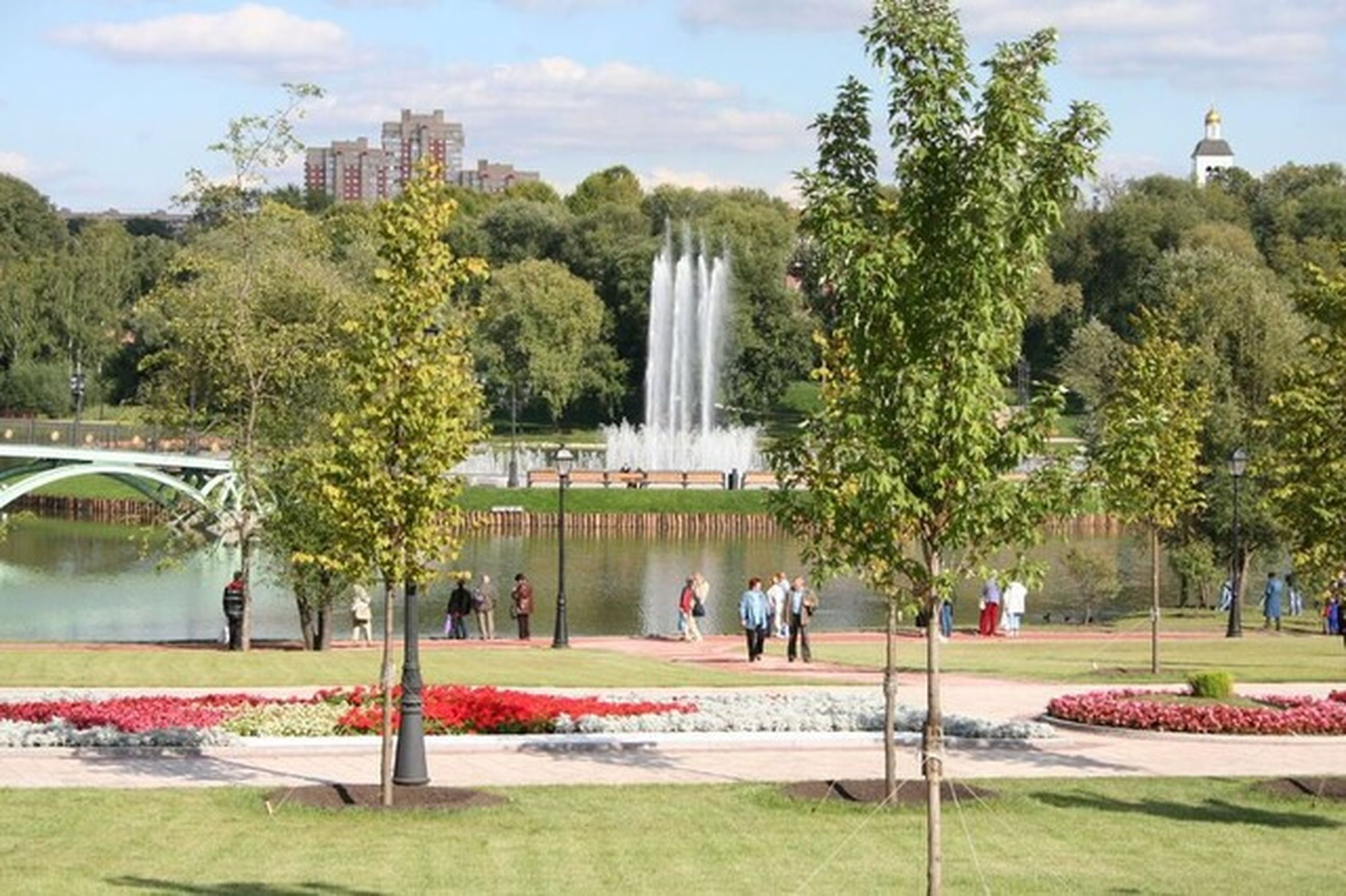 tree, fountain, large group of people, park - man made space, architecture, built structure, person, water, tourist, men, tourism, travel destinations, lifestyles, leisure activity, famous place, building exterior, motion, spraying, sky