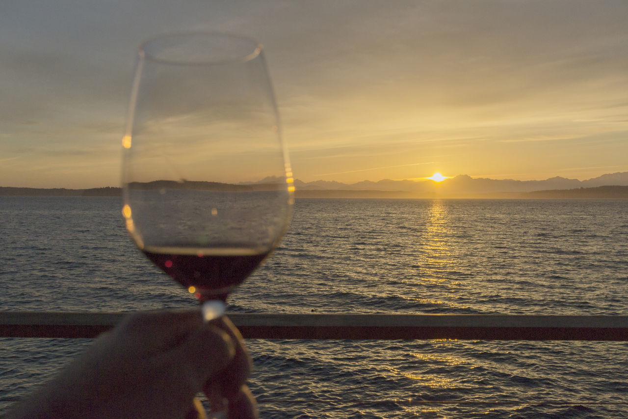 Focus on the sunset with red wine over the sea Alcohol Beauty In Nature Close-up Cruise Drink Drinking Glass Holding Horizon Over Water Human Hand Leisure Activity Lifestyles Nature Outdoors Red Wine Refreshment Sailing Scenics Sea Sky Sun Sunlight Sunset Water Wine Wineglass
