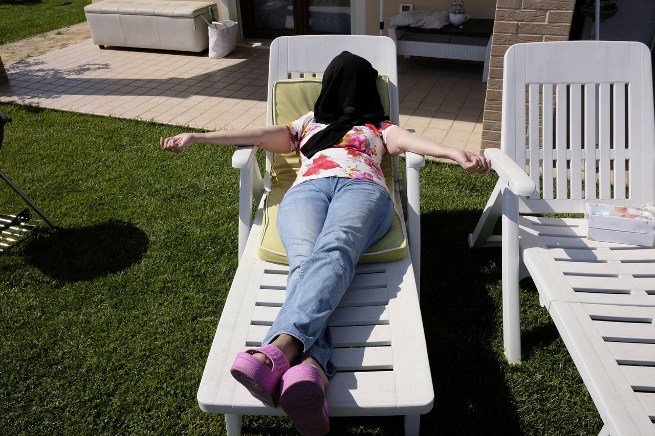 Sunbathing in the garden Architecture Building Exterior Built Structure Casual Clothing Day Deckchairs Full Length Grass Leisure Activity Lifestyles Outdoors Real People Rear View Spring Sunbathe