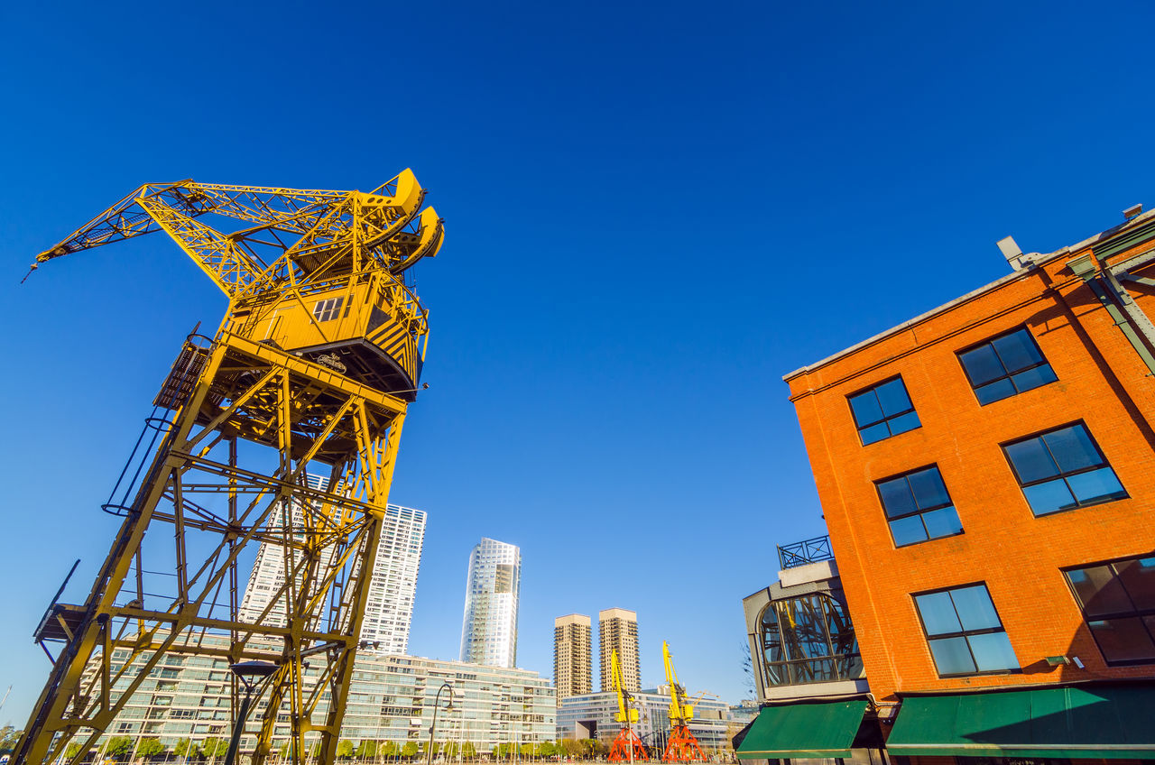 Crane At Construction Site In City Against Clear Blue Sky