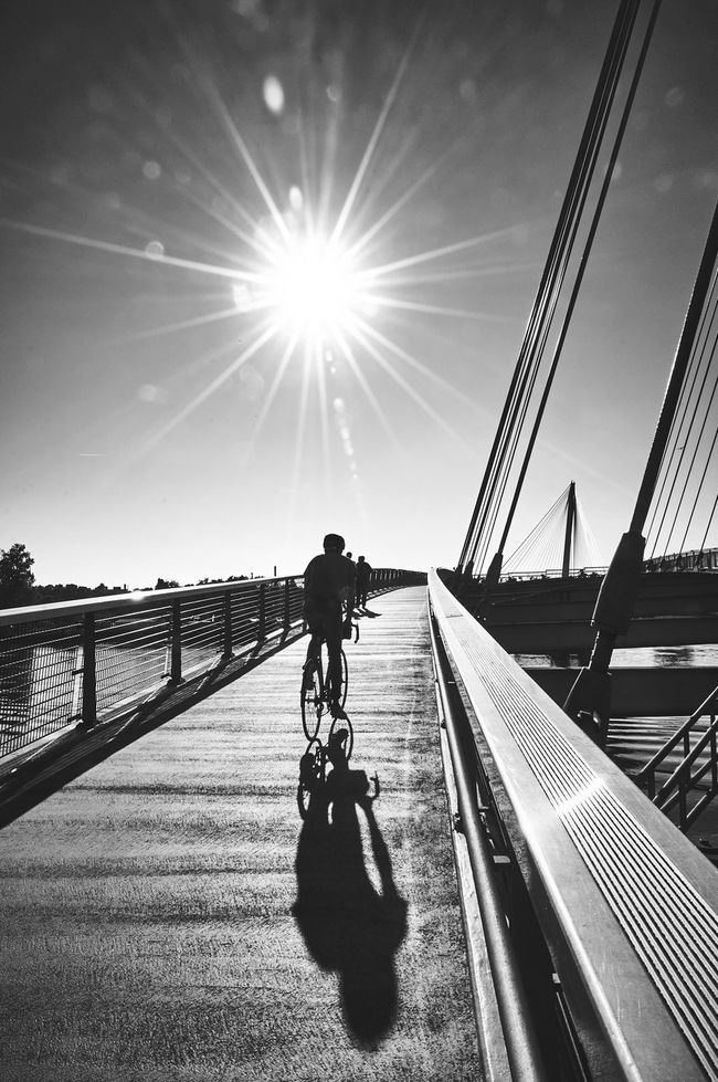 People And Places Streetphotography Sunlight Transportation Shadow Bridge - Man Made Structure Showcase September Lifestyles Leisure Activity Black And White Monochrome Photography Motion On The Move Riding Connection Sunbeam Clear Sky Bicycle Lens Flare Mode Of Transport Day CyclingUnites Borderline France Germany