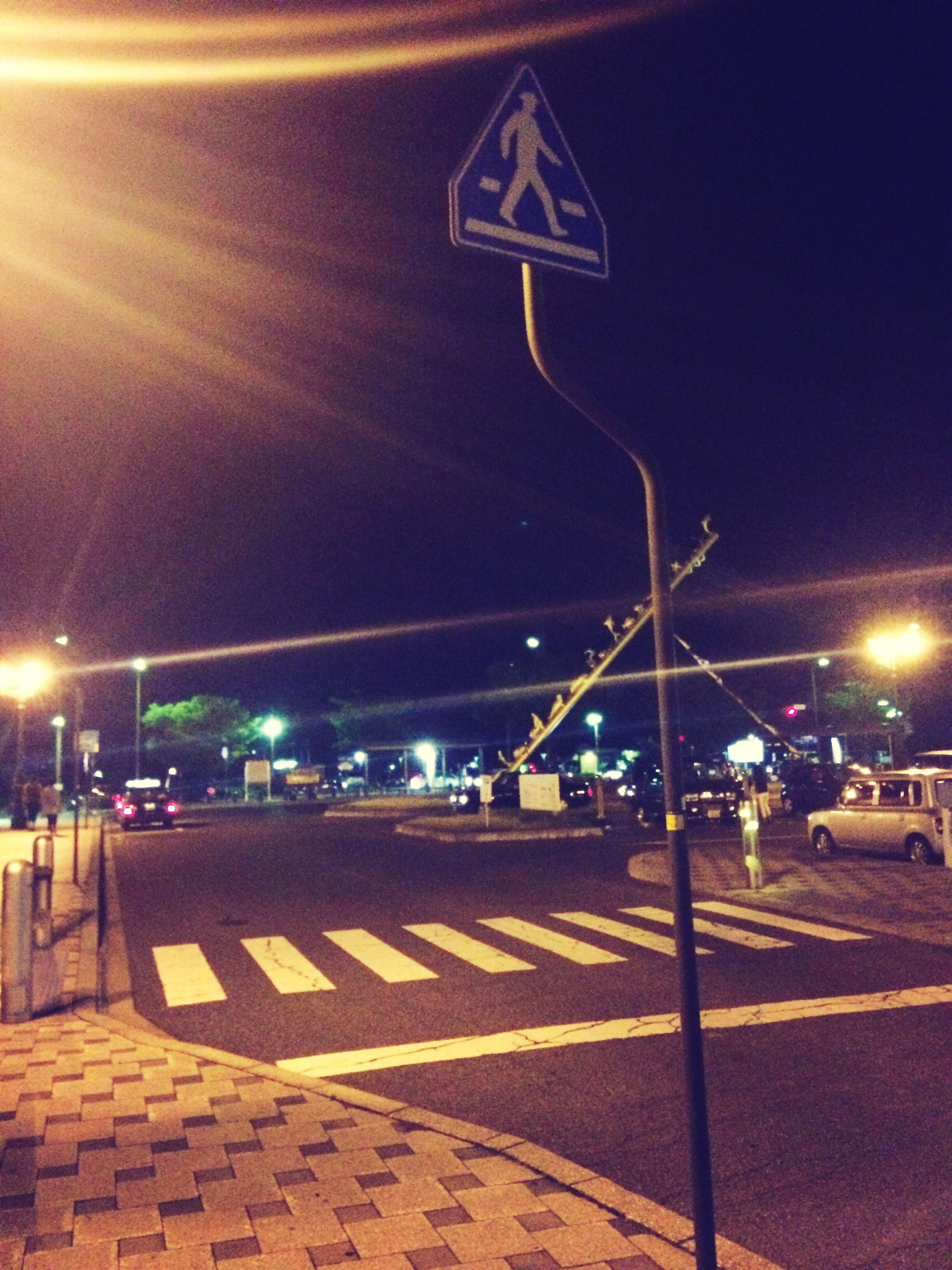 illuminated, night, street light, transportation, street, road, lighting equipment, road marking, road sign, the way forward, city street, guidance, city, car, communication, zebra crossing, arrow symbol, sky, text, sign