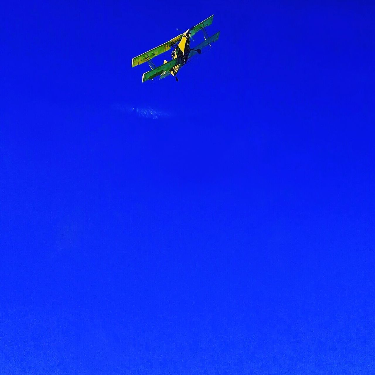 blue, low angle view, copy space, clear sky, mid-air, flying, outdoors, day, risk, air vehicle, airplane, sky, no people, nature