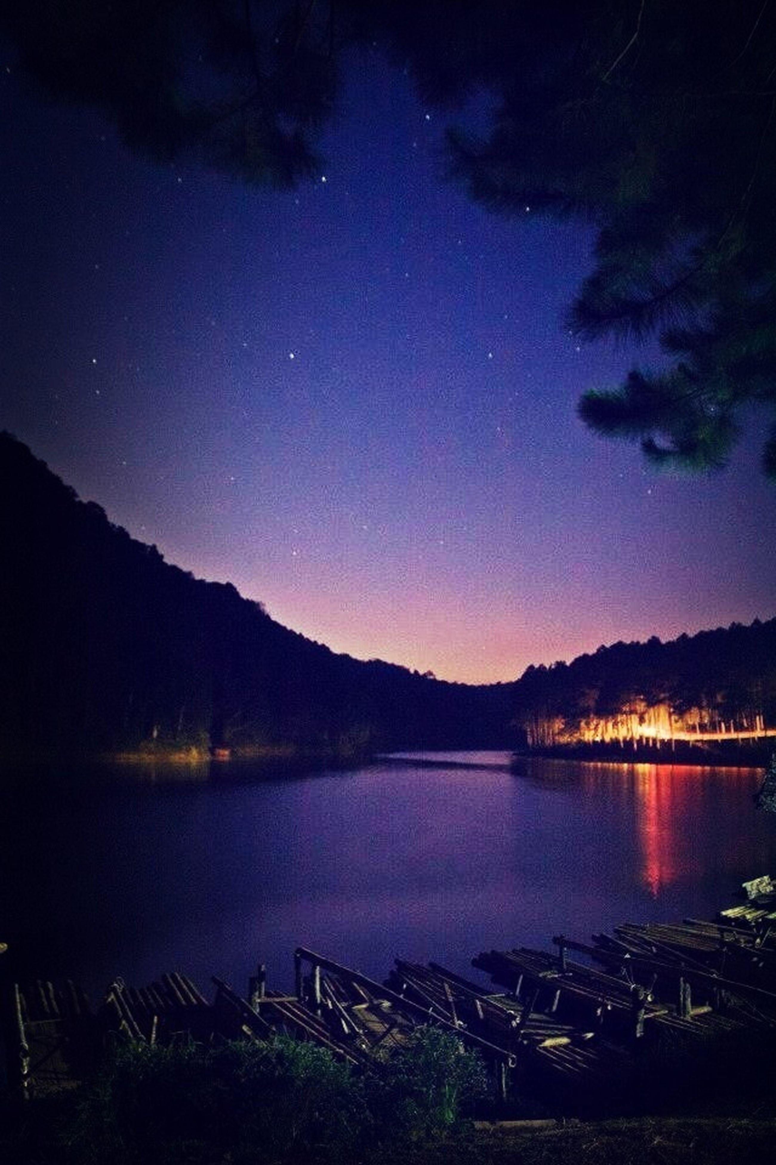 night, water, tranquil scene, scenics, tranquility, lake, beauty in nature, illuminated, mountain, reflection, sky, nature, idyllic, silhouette, tree, blue, mountain range, river, calm, dusk