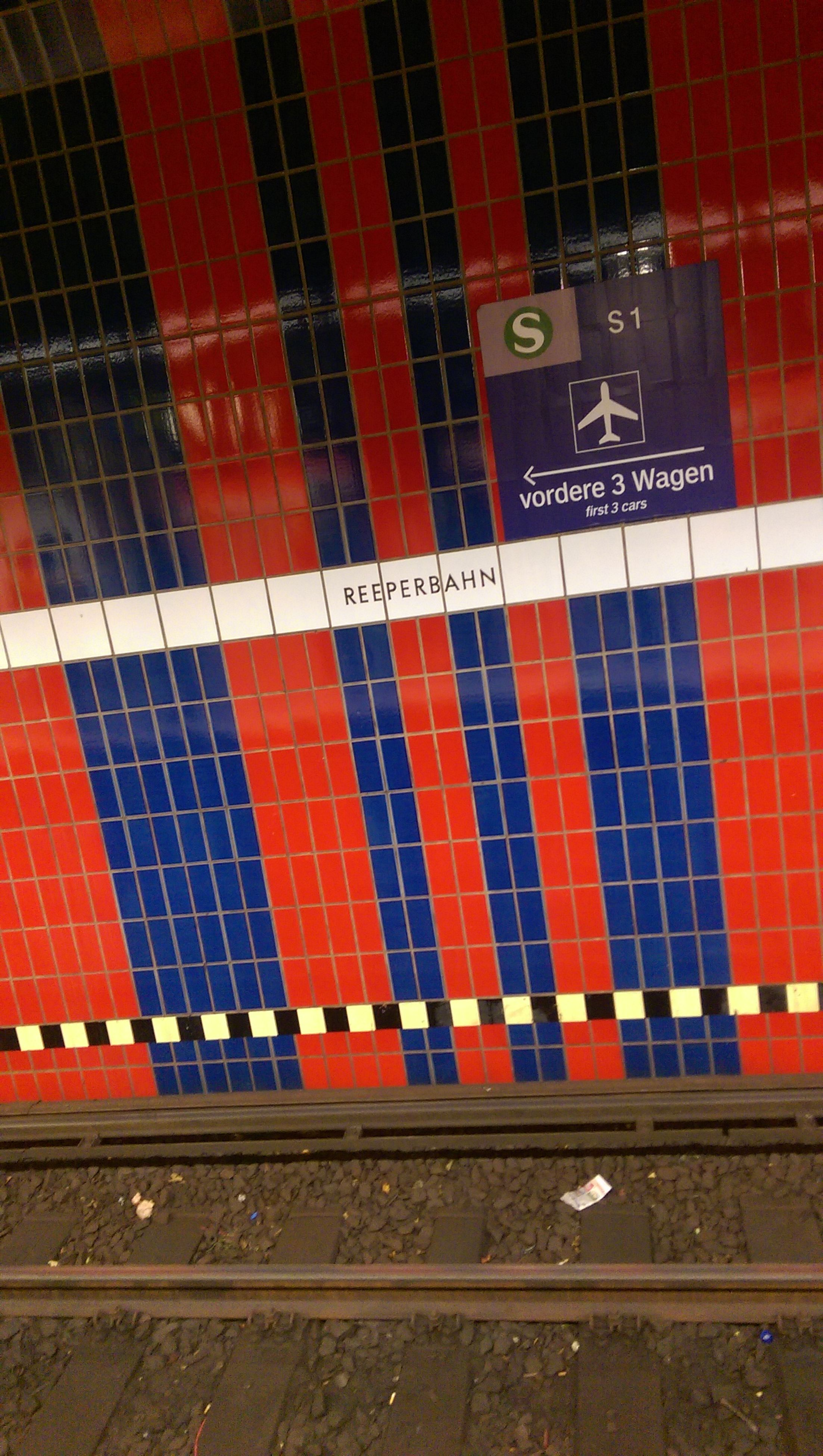 red, transportation, railroad station, indoors, communication, wall - building feature, public transportation, pattern, text, railroad station platform, subway station, number, rail transportation, western script, railroad track, in a row, built structure, tile, multi colored, no people