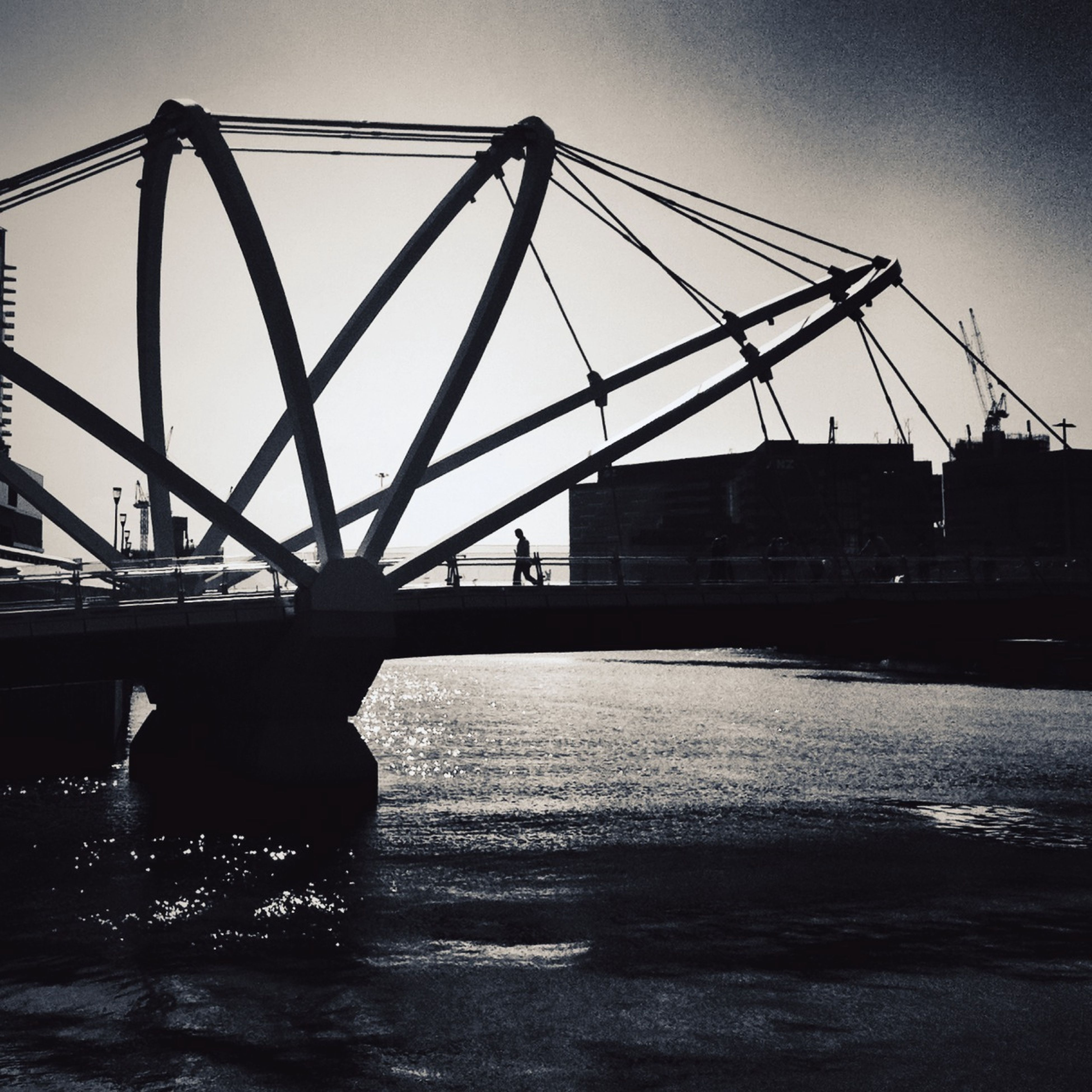 water, transportation, sky, bridge - man made structure, silhouette, built structure, connection, clear sky, river, sunset, architecture, engineering, metal, men, outdoors, leisure activity, mode of transport, dusk