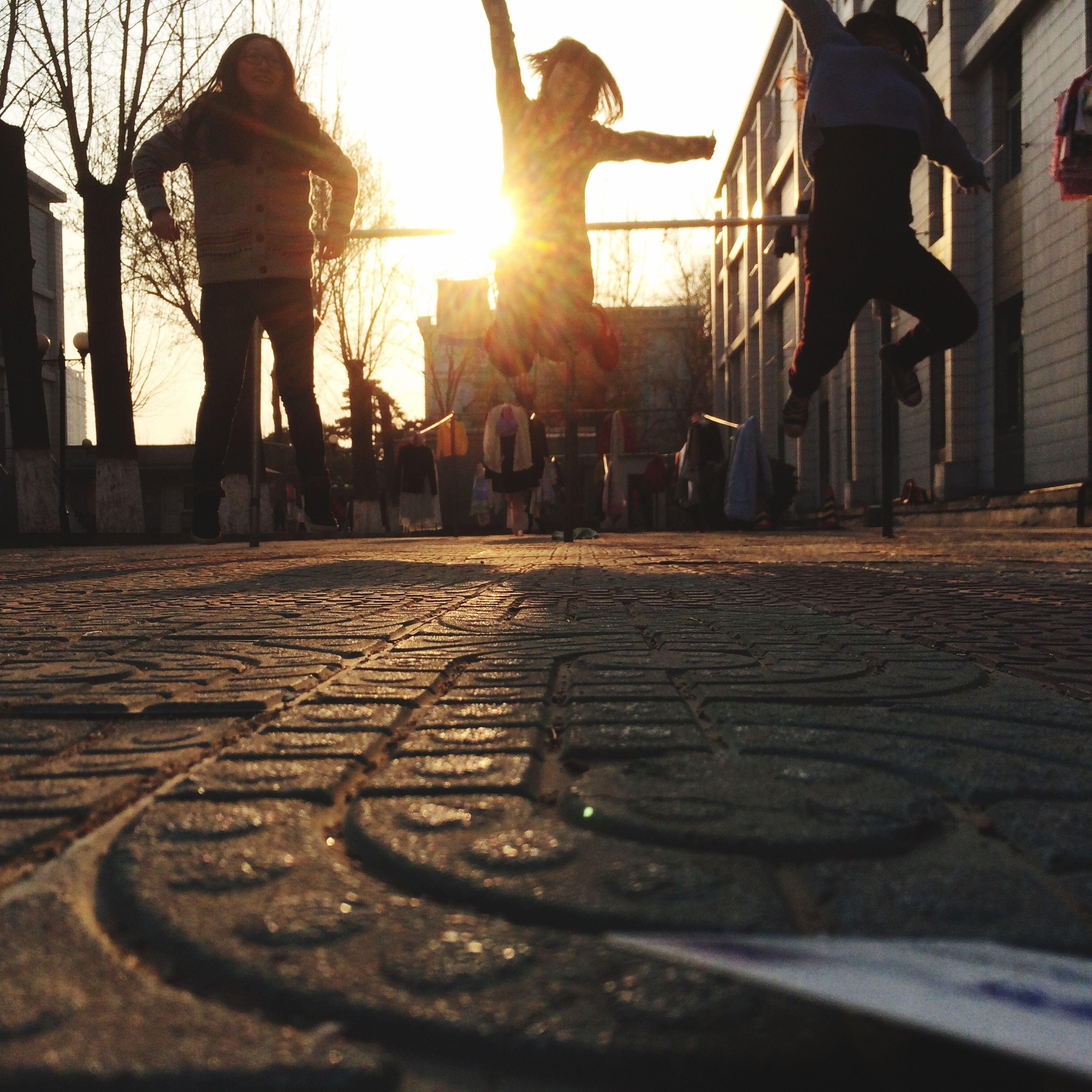 built structure, architecture, building exterior, lifestyles, leisure activity, sunlight, men, sunset, sun, sunbeam, person, cobblestone, walking, sky, shadow, street, city