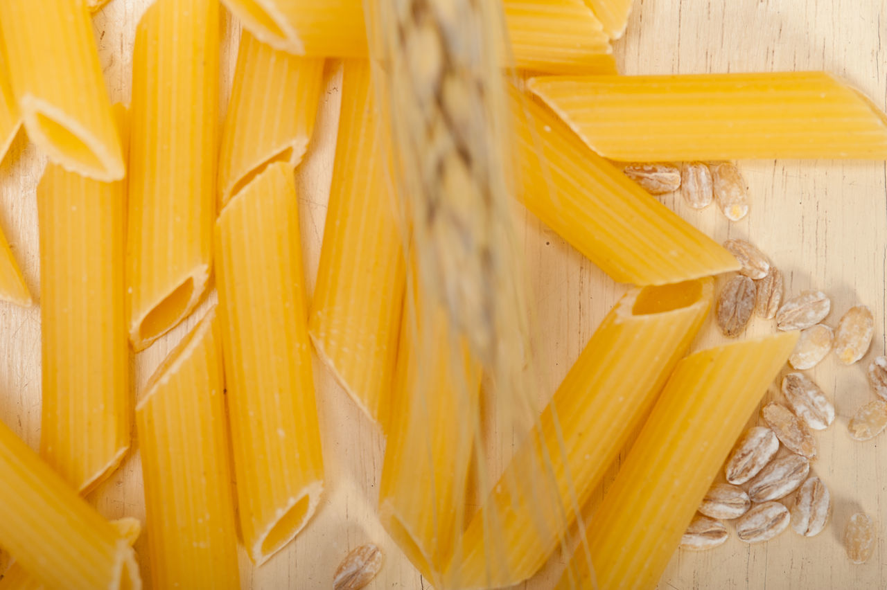 Directly Above Shot Of Pasta And Wheat On Wooden Table